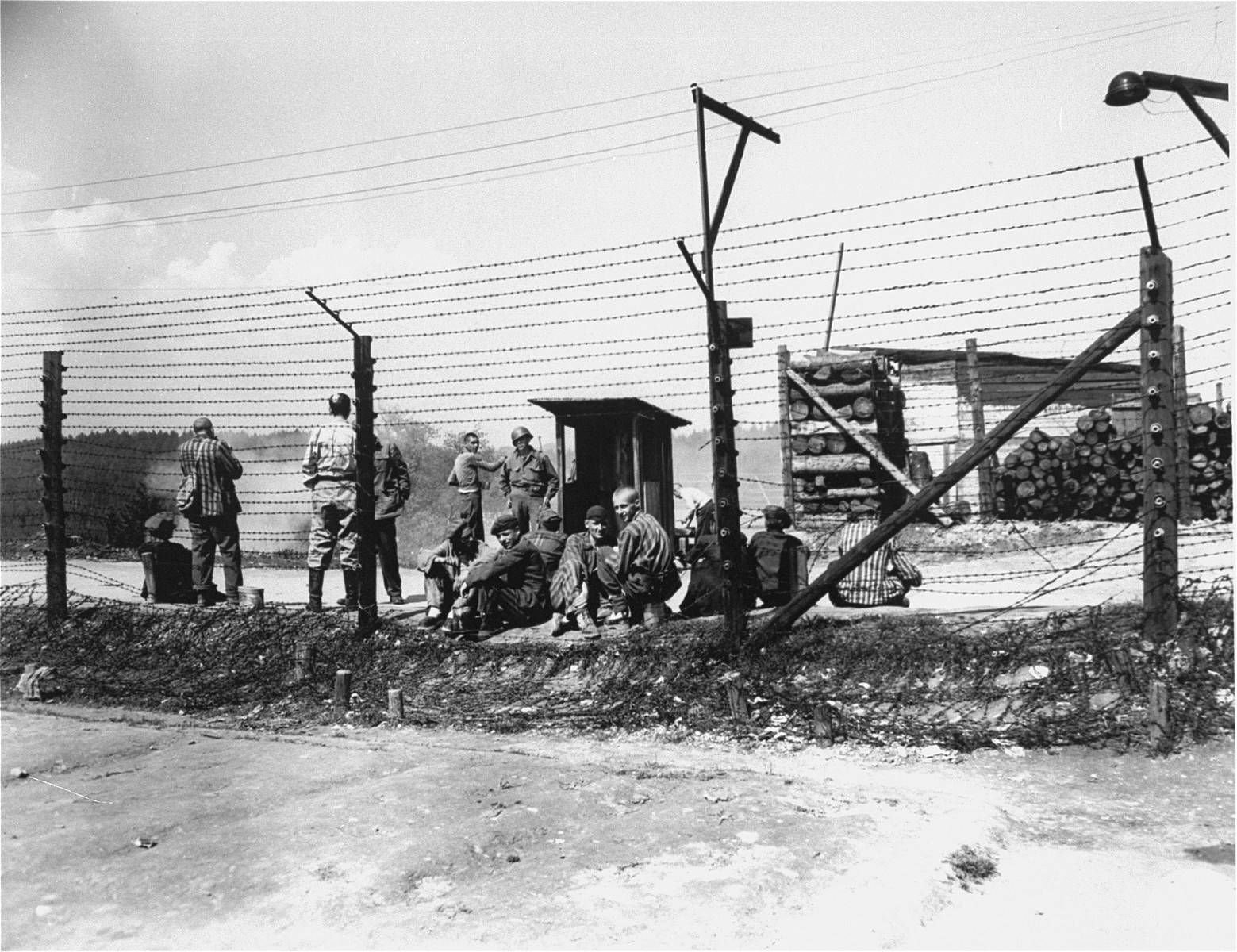 Survivors gather beside a barbed wire fence in Mauthausen while an American soldier stands guard.
