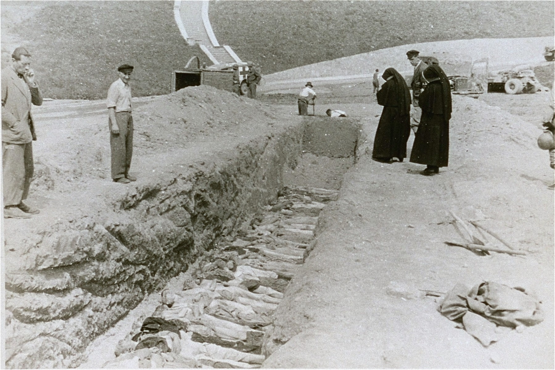 Nuns from a nearby convent view the bodies of former inmates in an open mass grave that has been prepared by Austrian civilians at the Mauthausen concentration camp.