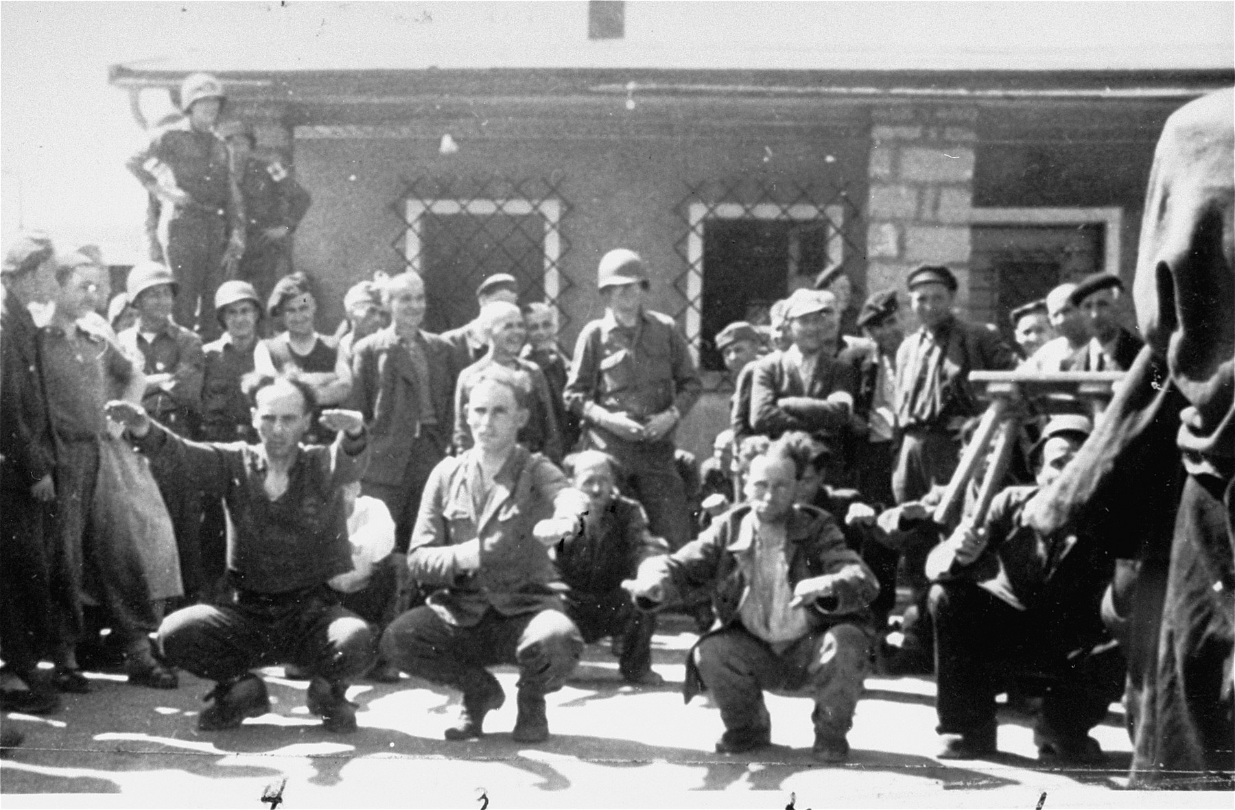 Survivors and American soldiers watch as former SS guards are forced to do calisthenics at the Gusen concentration camp.