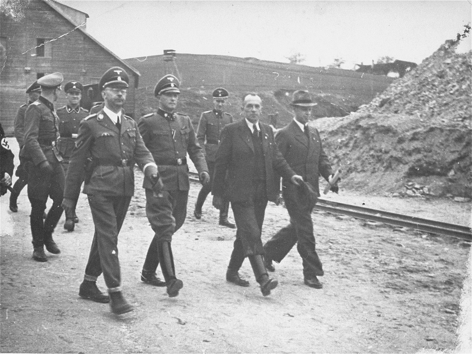 Reichsfuehrer SS Heinrich Himmler and his entourage inspect the Wiener Graben quarry during an official tour of the Mauthausen concentration camp.  Himmler is pictured first on the left.  Next to him is SS Sturmbannfuehrer Franz Ziereis, Commandant of Mauthausen.