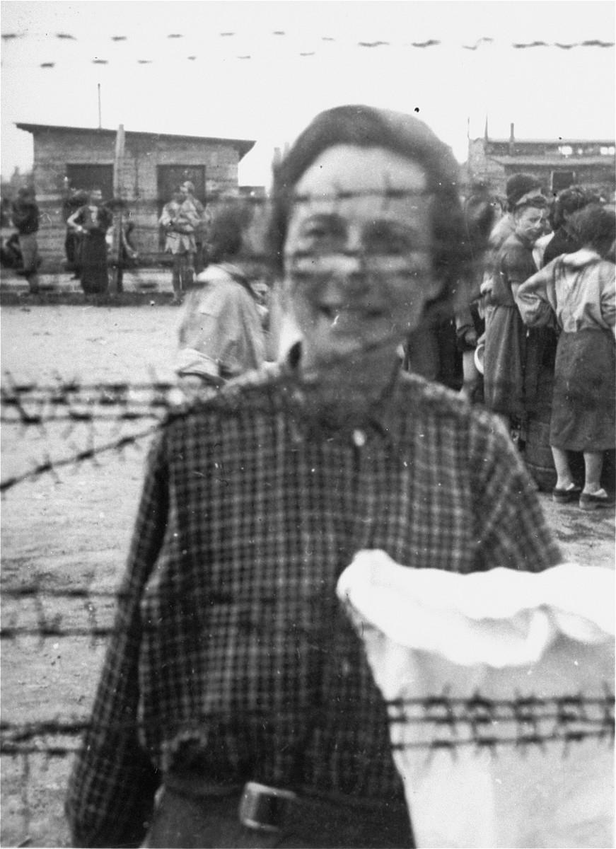 Portrait of a female survivor of Mauthausen standing behind the barbed wire fence.  Pictured is Etta Krevstlen.