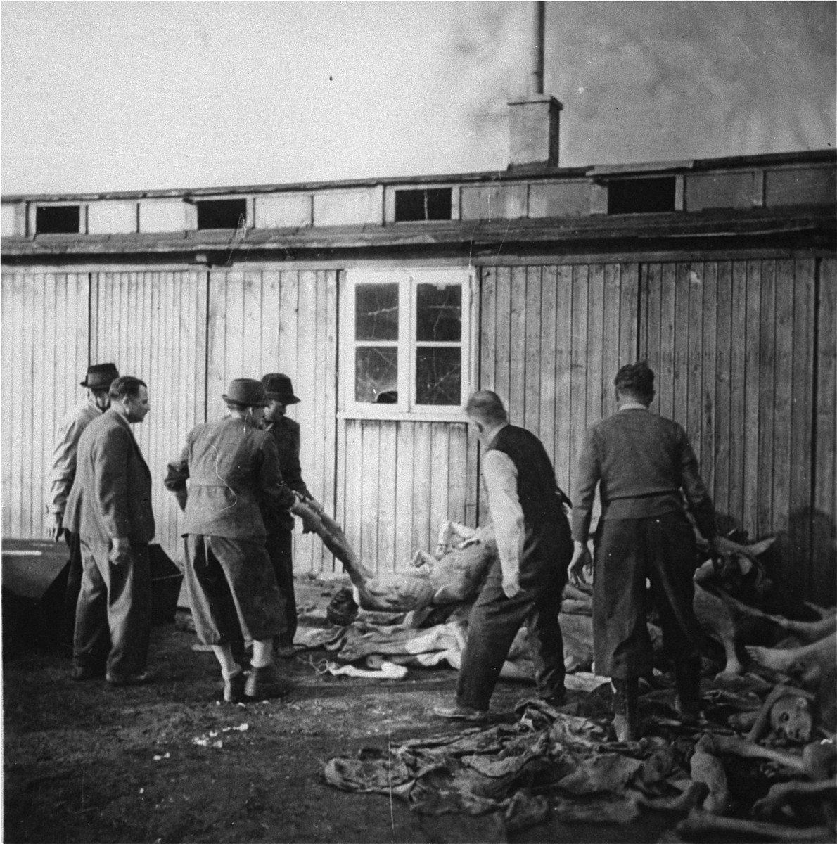 "On orders from the U.S. Army, Austrian citizens remove corpses from the ""Russian camp"" section of Mauthausen for burial in a mass grave."