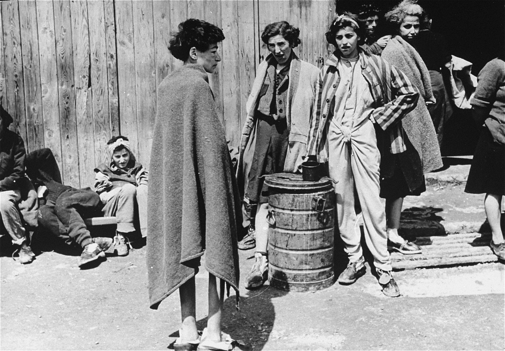 In the women's camp at Mauthausen, survivors stand around the entrance to a barracks.