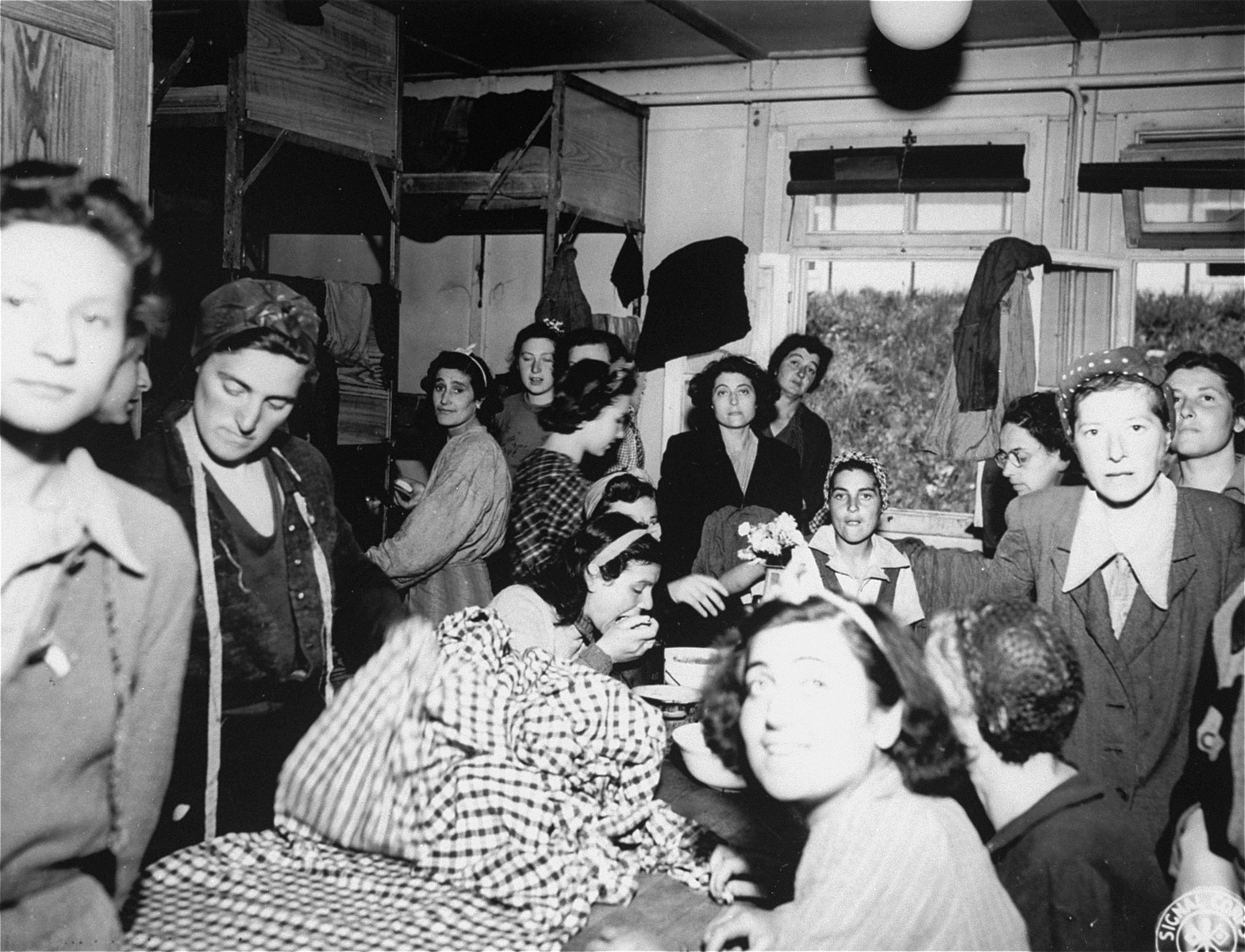 Female survivors wearing civilian clothing gather in a barrack after the liberation of Mauthausen.