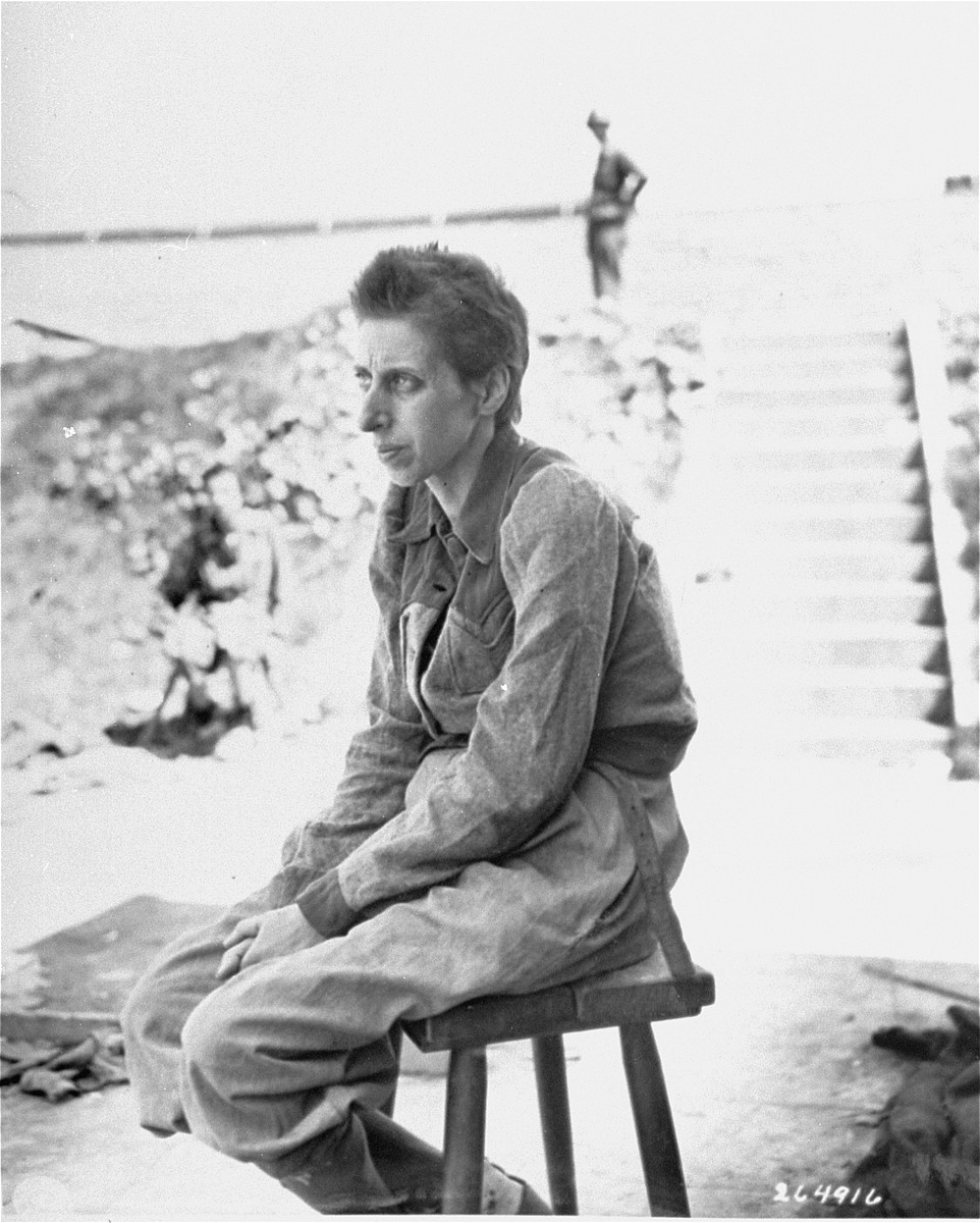 A female survivor poses outside sitting on a stool in the newly liberated Mauthausen concentration camp.