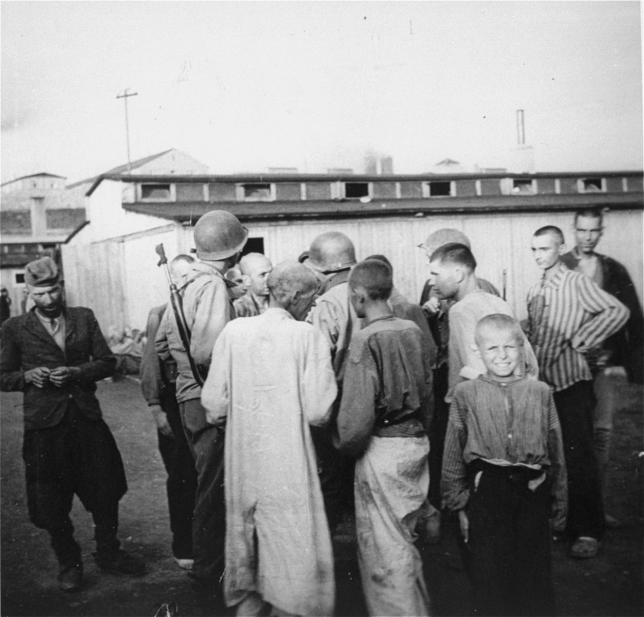 "Mauthausen survivors in the ""Russian camp"" greet American soldiers.    The main camp of Mauthausen is visible on the heights behind the barracks."