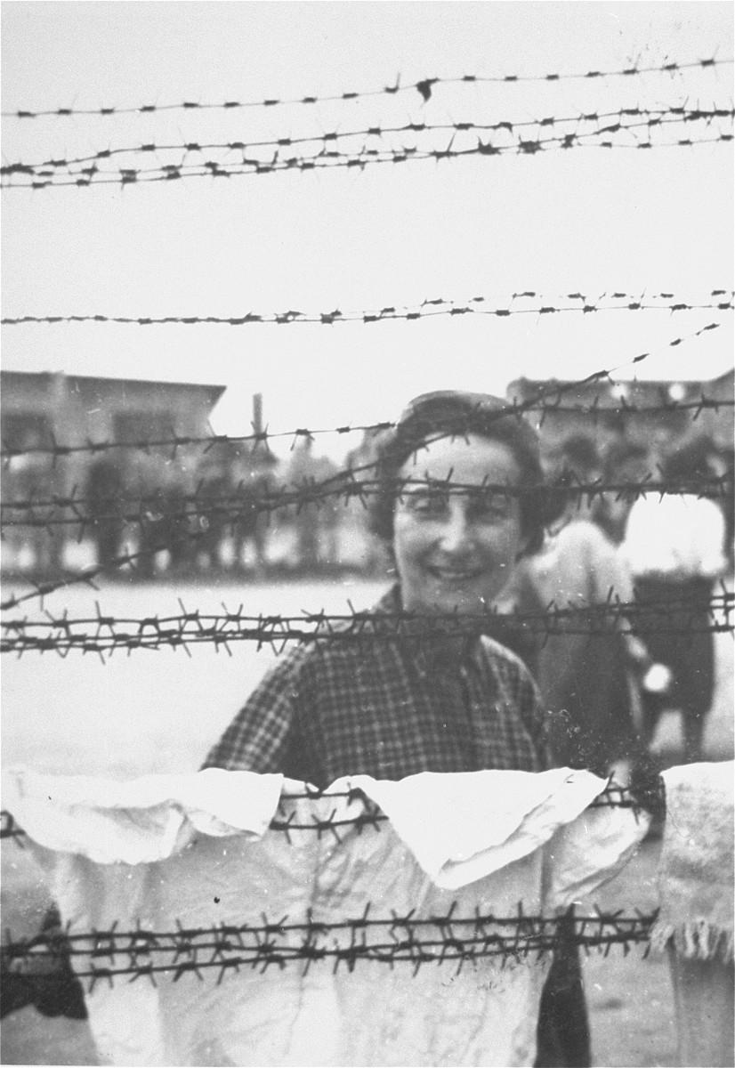 Etta Krevstlen, a survivor in Mauthausen, poses behind a barbed wire fence.