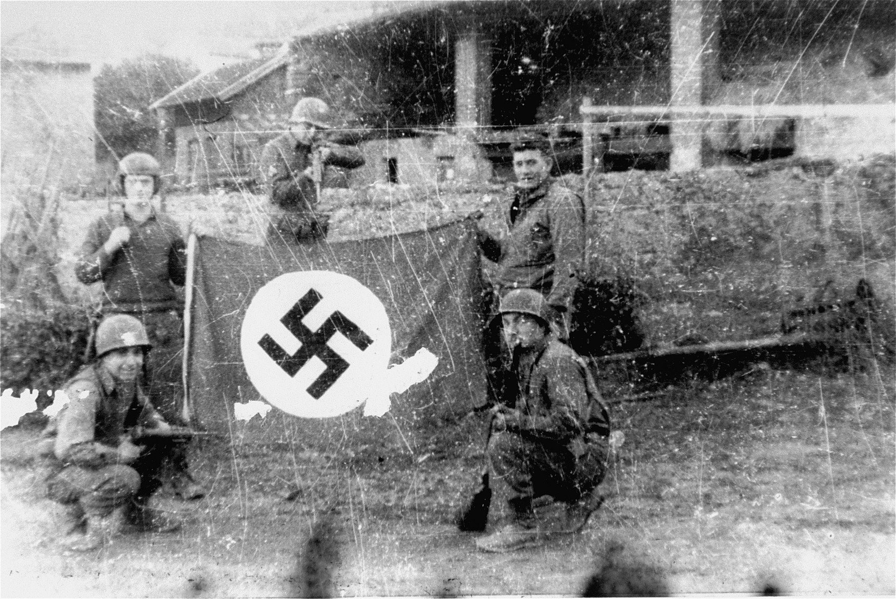 American soldiers pose with a captured Nazi flag after liberating the Mauthausen concentration camp.