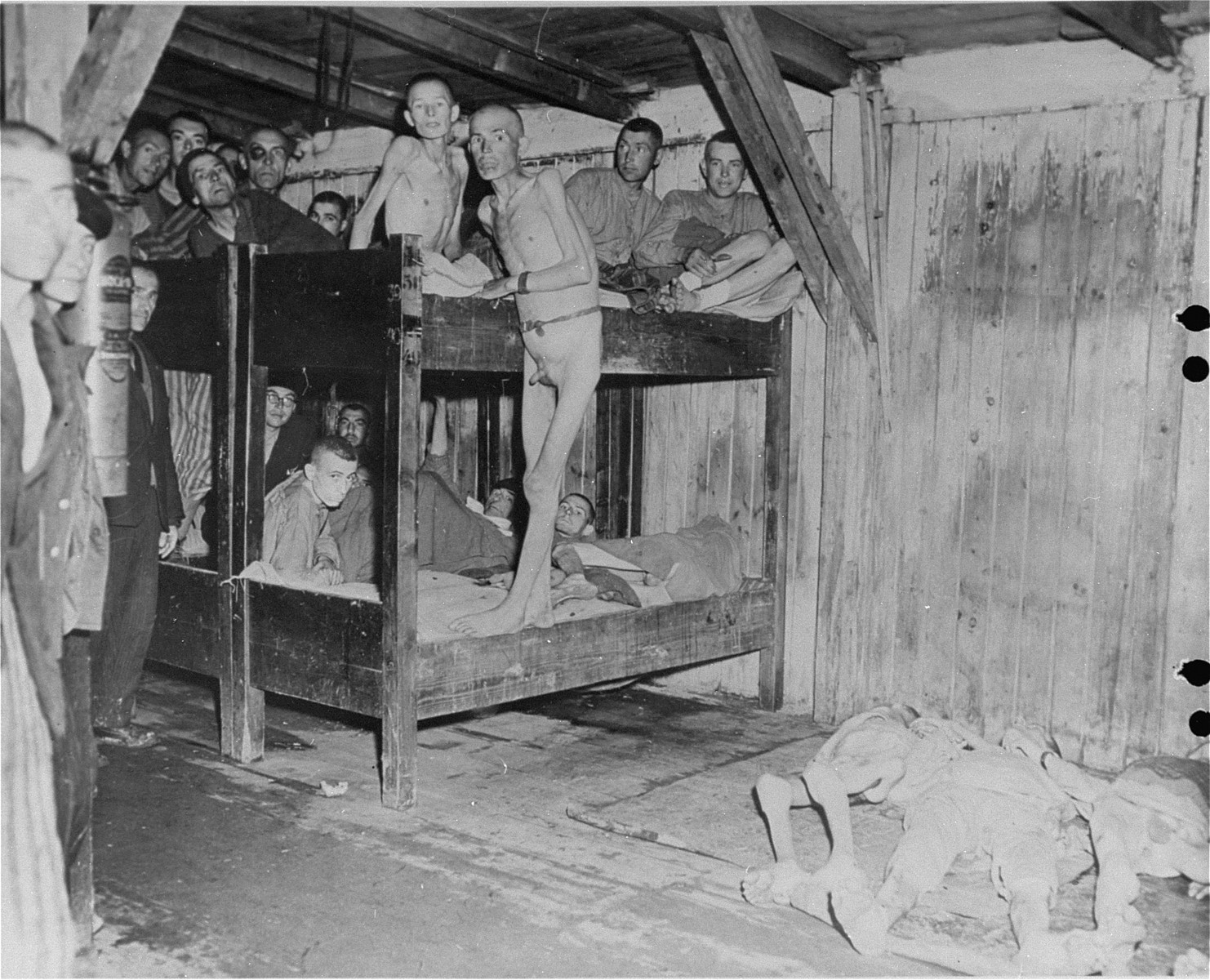 Survivors of the Mauthausen concentration camp pose inside a barracks after liberation.  The bodies of dead prisoners have been piled in the open area to the left.