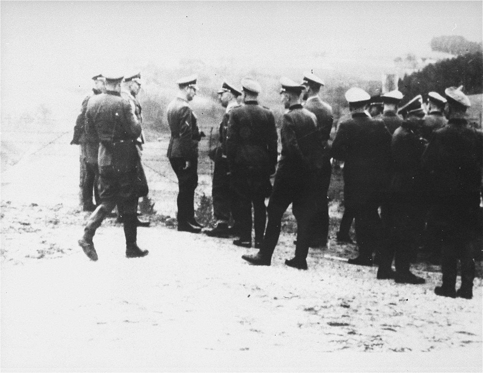 Reichsfuehrer SS Heinrich Himmler speaks to a member of his entourage while viewing the quarry during an inspection tour of the Mauthausen concentration camp.  Among those pictured are Heinrich Himmler, Ernst Kaltenbrunner and August Eigruber.