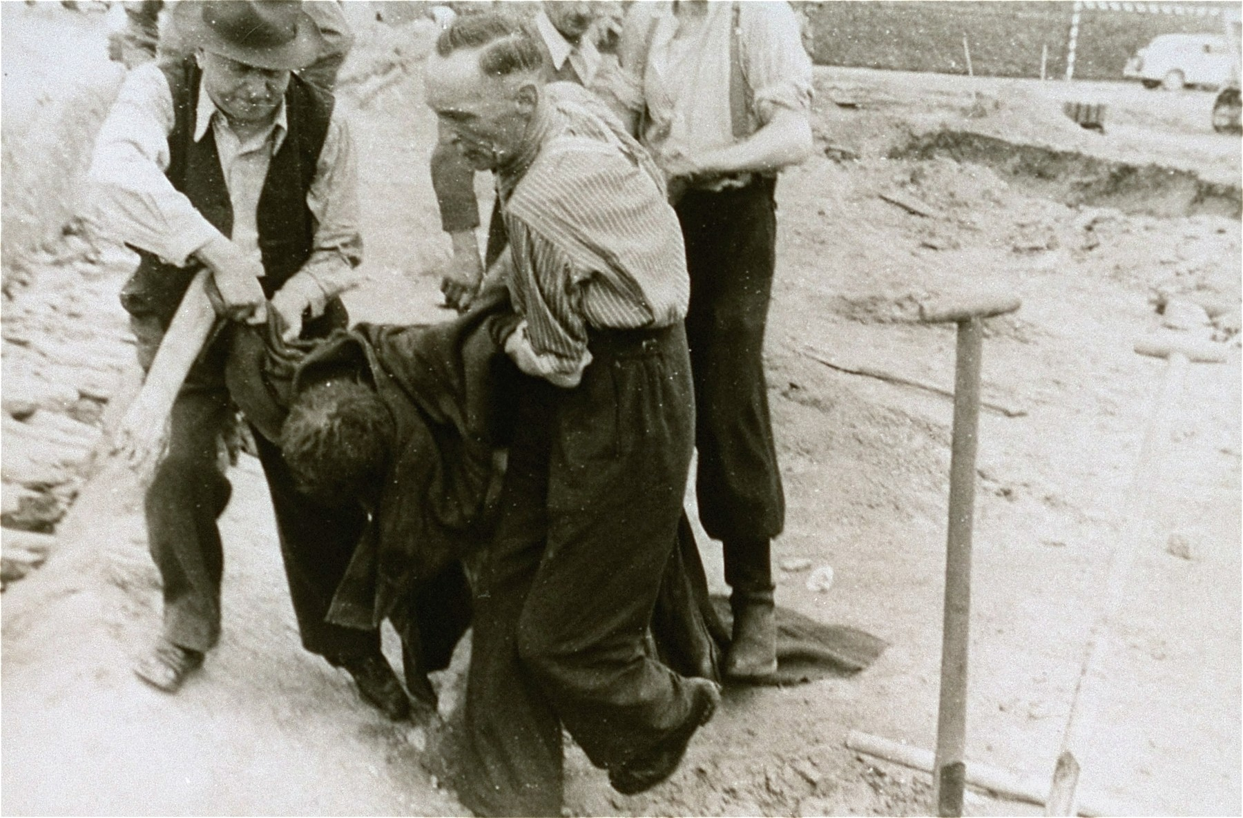 Austrian civilians carry the body of a former inmate to a mass grave in the Gusen concentration camp.