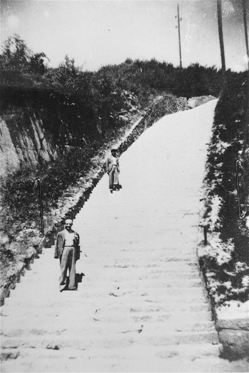 "Two survivors pose on the stone ""steps of death"" (Todesstiege) in the Mauthausen Wiener Graben quarry."