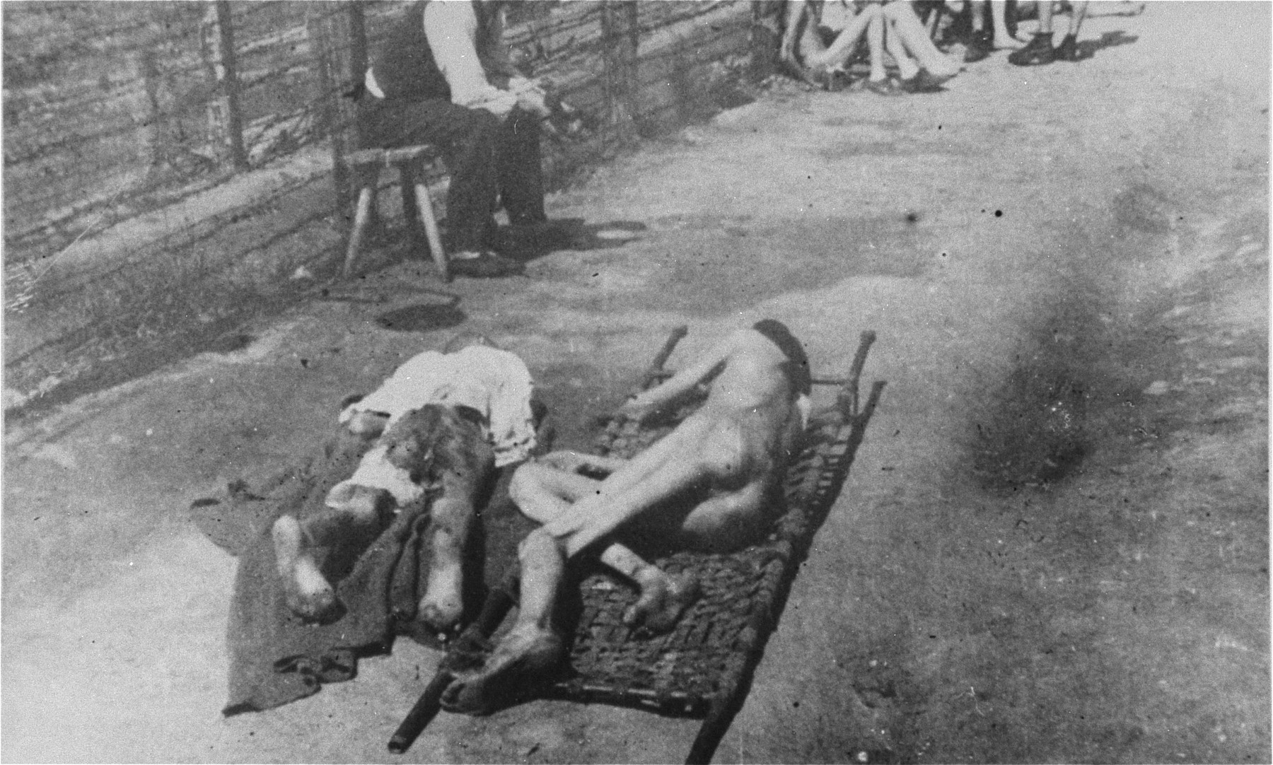 Two bodies lie on stretchers in Mauthausen after liberation.