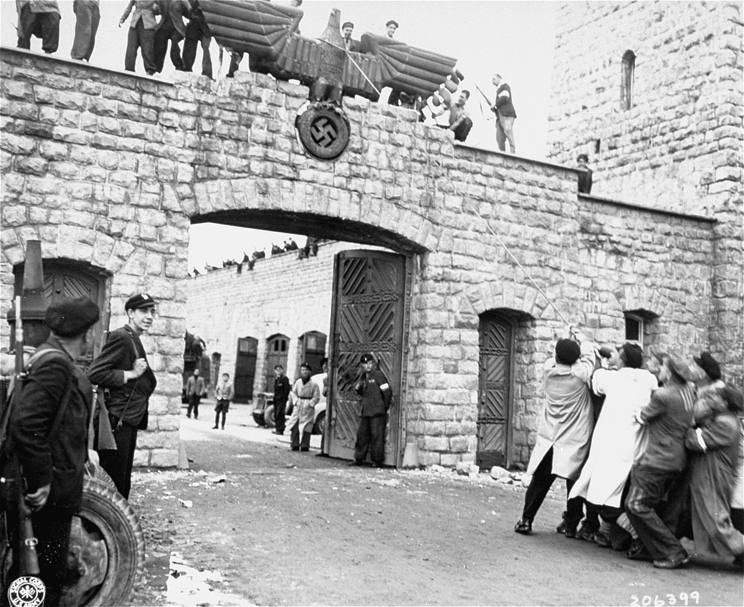 Spanish survivors take down the Nazi eagle that hangs above the entrance to the SS compound in Mauthausen on the day of liberation.   Pictured on top of the eagle is Tello; Choumoff (wearing an armband) is on the right.
