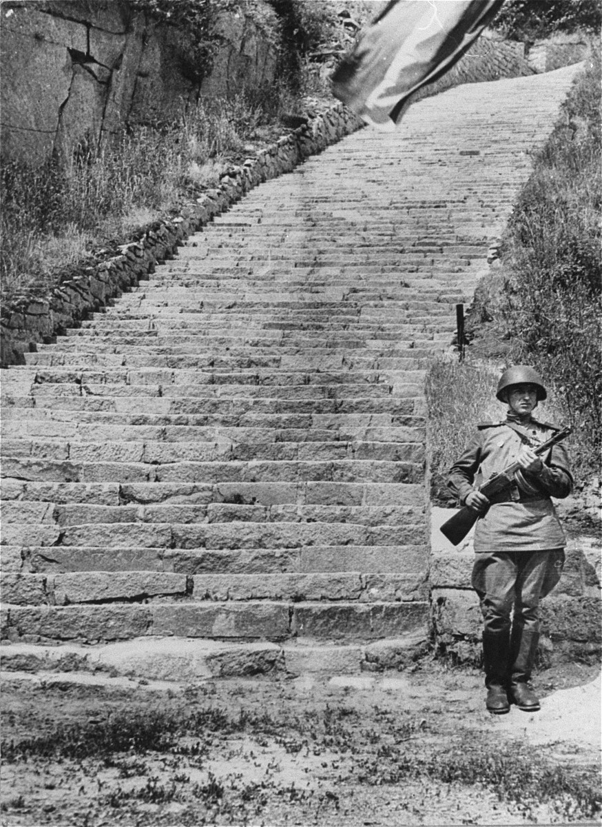 "A Soviet honor guard stands next to the stone ""stairs of death"" (Todesstiege) in the Wiener Graben quarry at the Mauthausen concentration camp."