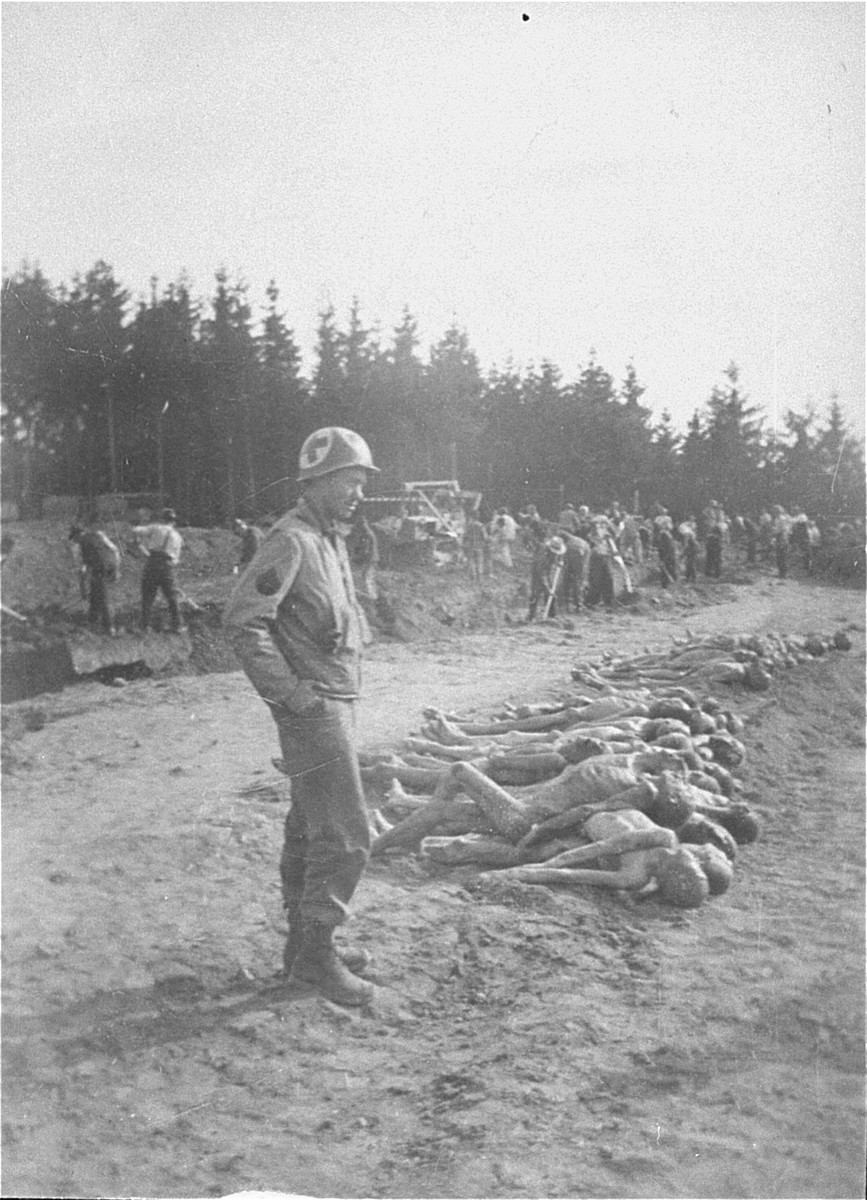 An American medic watches as Austrians civilians bury the corpses of prisoners from Mauthausen in mass graves.