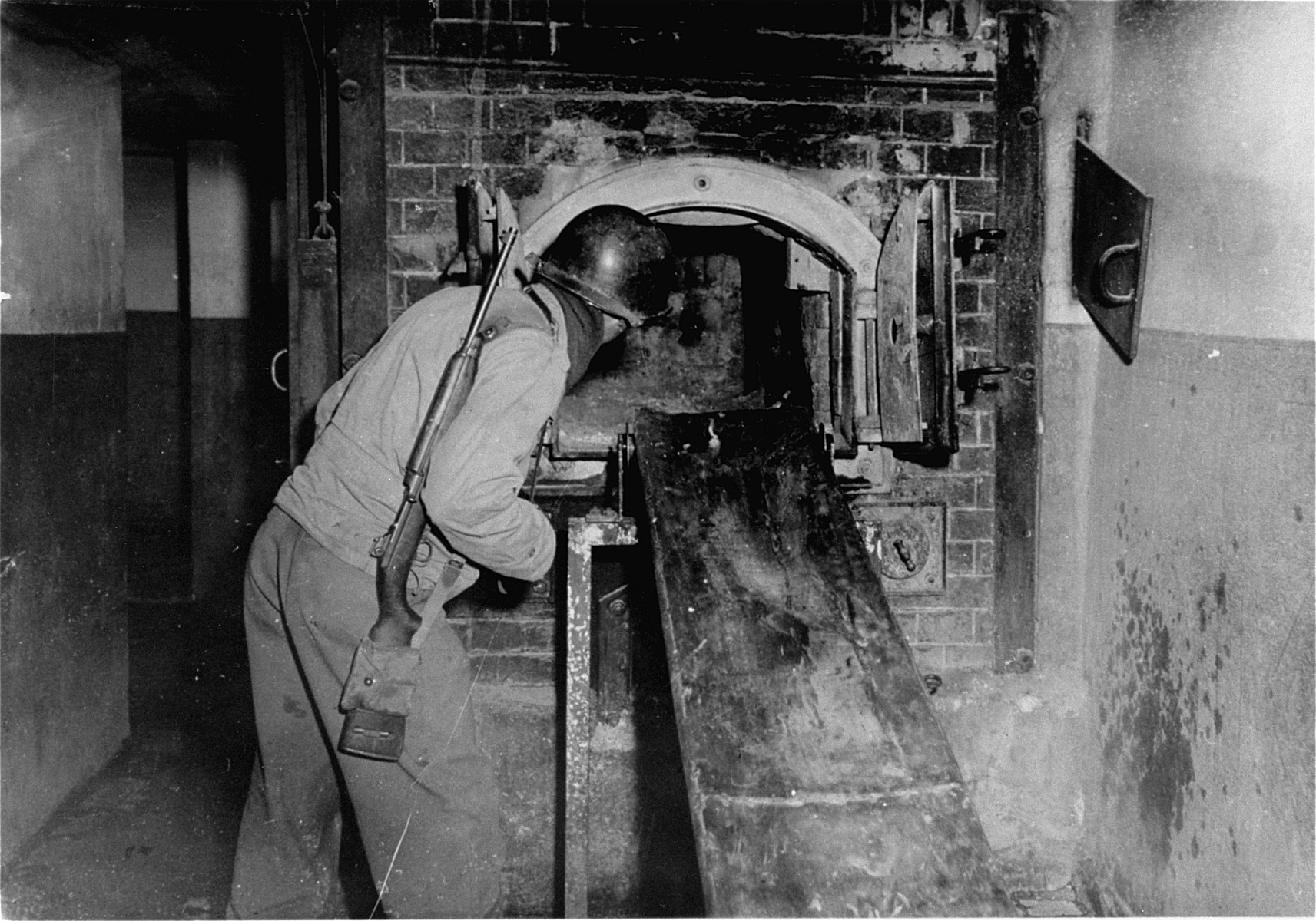 An American soldier peers into an oven that has been cleaned of human remains.