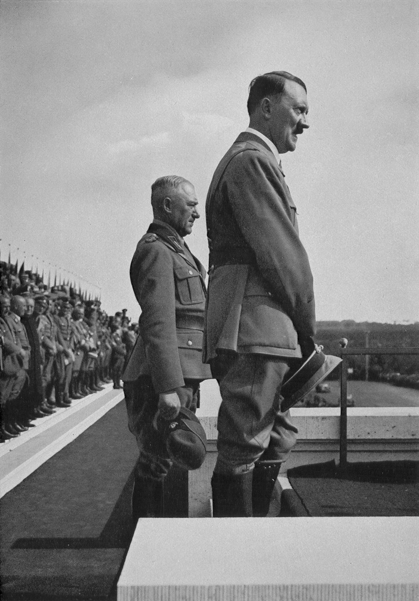 Chancellor Adolf Hitler and Reichsarbeitsfuehrer Generalmajor Konstantin Hierl stand before 47,000 members of the German Labor Service at Reichsparteitag (Reich Party Day) ceremonies in Nuremberg.