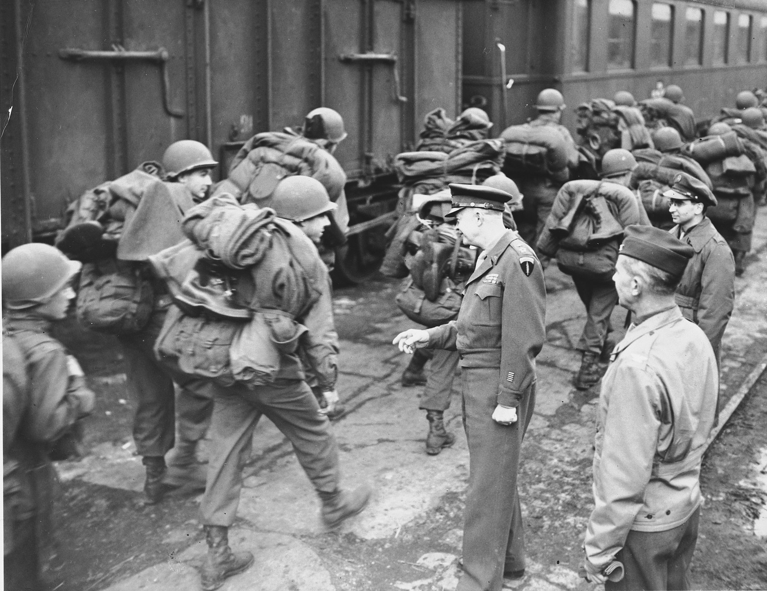General Dwight D. Eisenhower talks to US troops who are marching with their gear alongside a train.