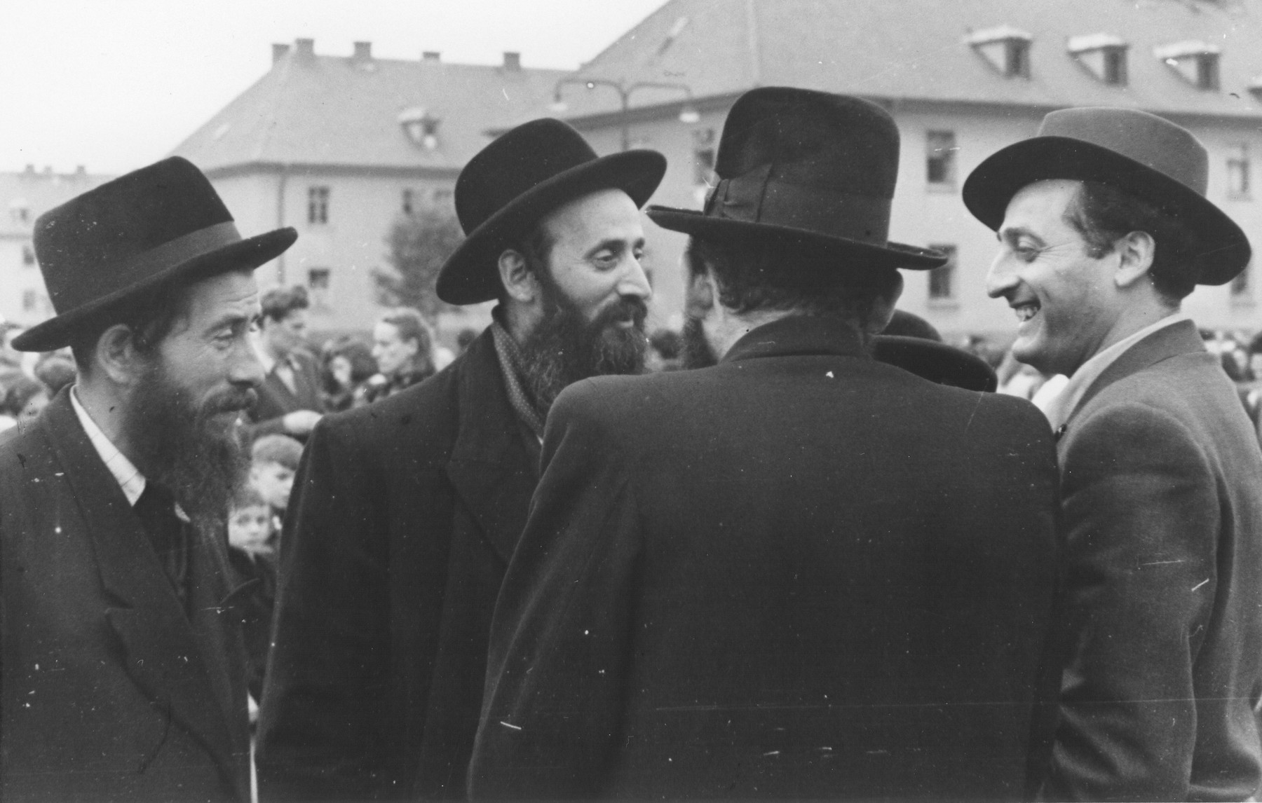 A group of rabbis converses outside at the Bergen Belsen displaced persons camp during a demonstration protesting the return of the Exodus 1947 passengers to Germany.   Among those pictured are Zvi Helfgot [Azaria] (right), Israel-Moshe Olewski (back to photographer).  Also pictured is the Sorvosher Ruv, Rabbi Chaim Meisels, center.