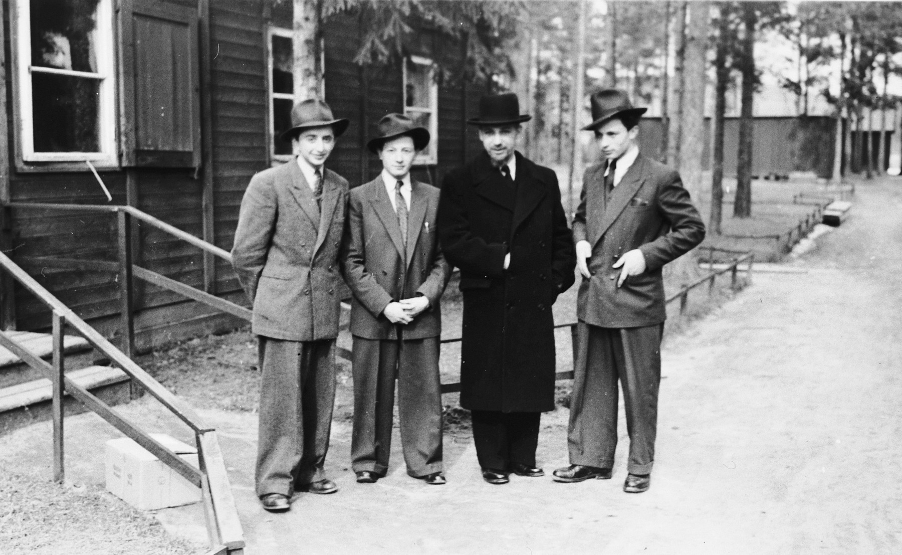 Four religious Jewish displaced persons stand in front of a barracks in a kosher center in Sweden.  Among them is a Romanian rabbi who assisted the others in getting visas.