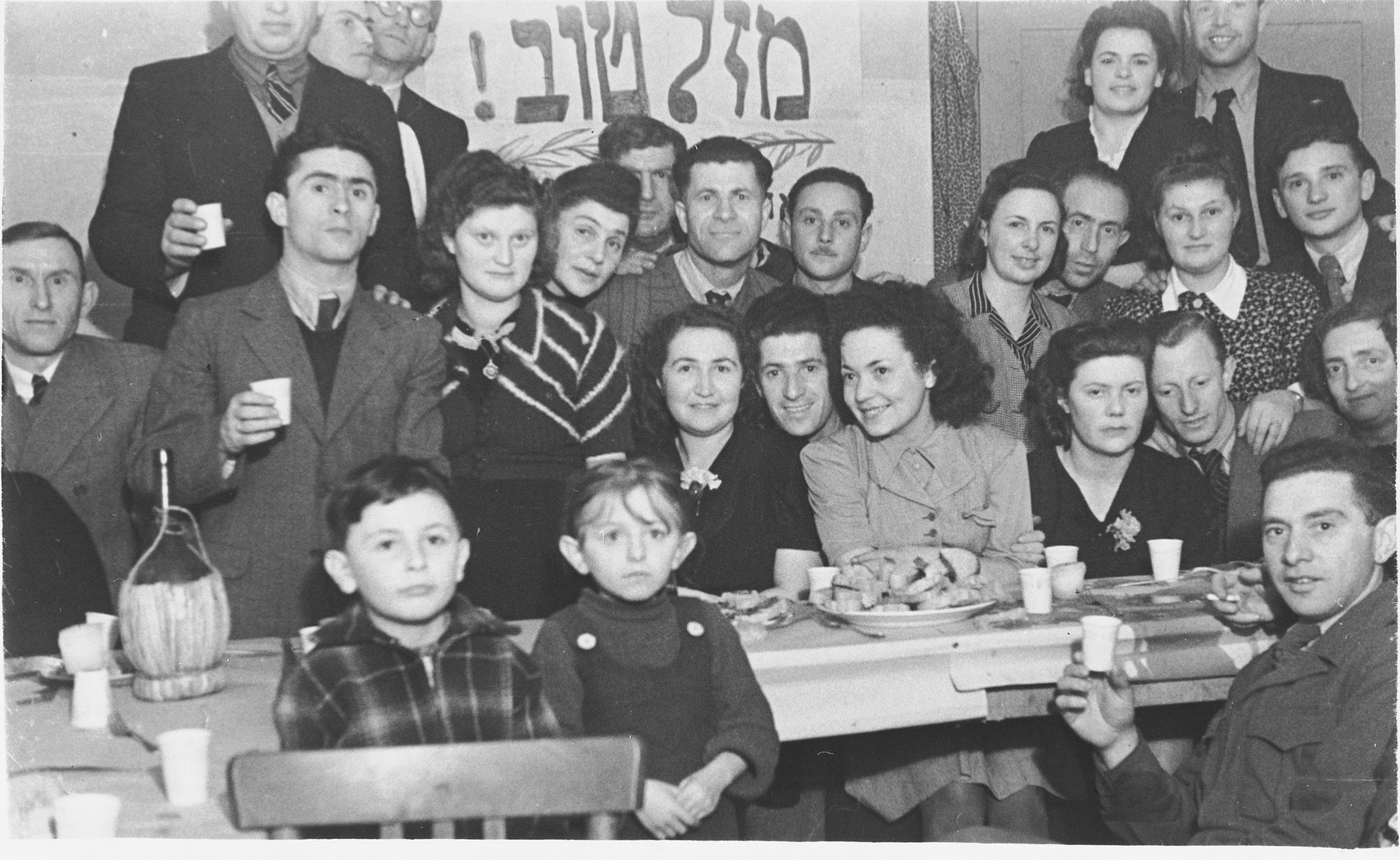 Jewish DPs at the kibbutz hachshara (Zionist collective) in Ponte Emma (near Florence), are gathered around a table during a wedding celebration for two of their members.
