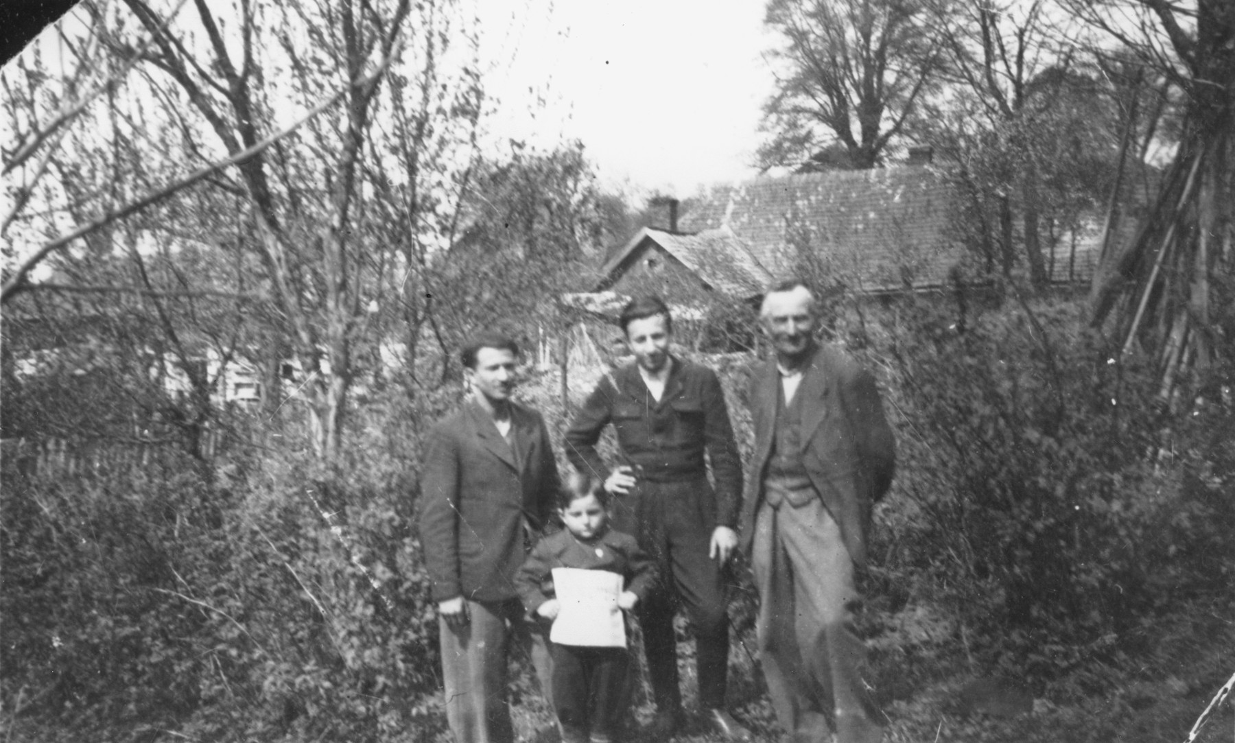 Nathan Berliner (center), a Jewish survivor, who during the German occupation of Poland had lived in hiding in Lancut, poses with his rescuer, Mr. Spiwak (right), who allowed him to live in his barn.  Also pictured is Beniek Kleinminc (left) and Itzhak Gerstein (in front).