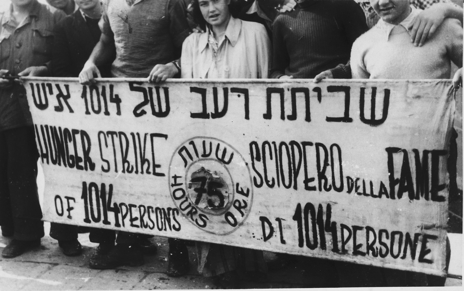 Jewish DPs in La Spezia harbor are gathered behind a banner announcing their hunger strike to protest British immigration policy in Palestine.