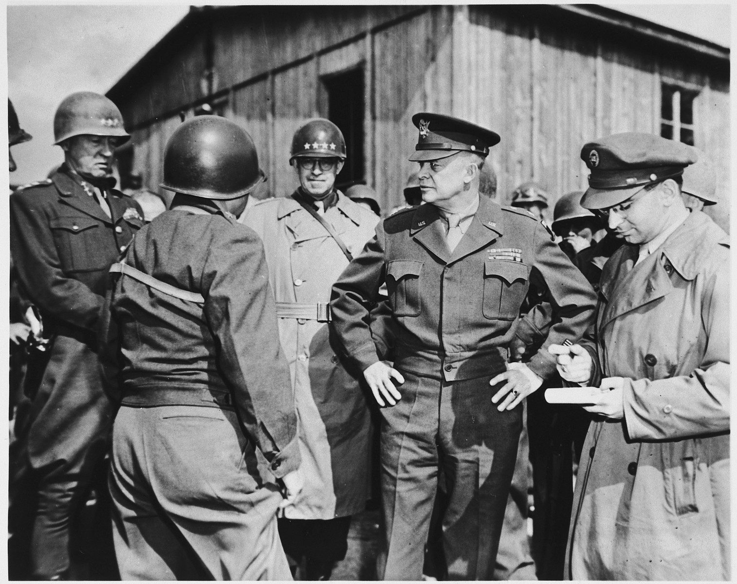 "High-ranking U.S. Army officers inspect the newly liberated Ohrdruf concentration camp.  Among those pictured are: Generals Dwight D. Eisenhower, George Patton and Omar Bradley.  Also pictured is Jules Grad, correspondent for the U.S. Army newspaper, ""Stars and Stripes"" (at the far right)."