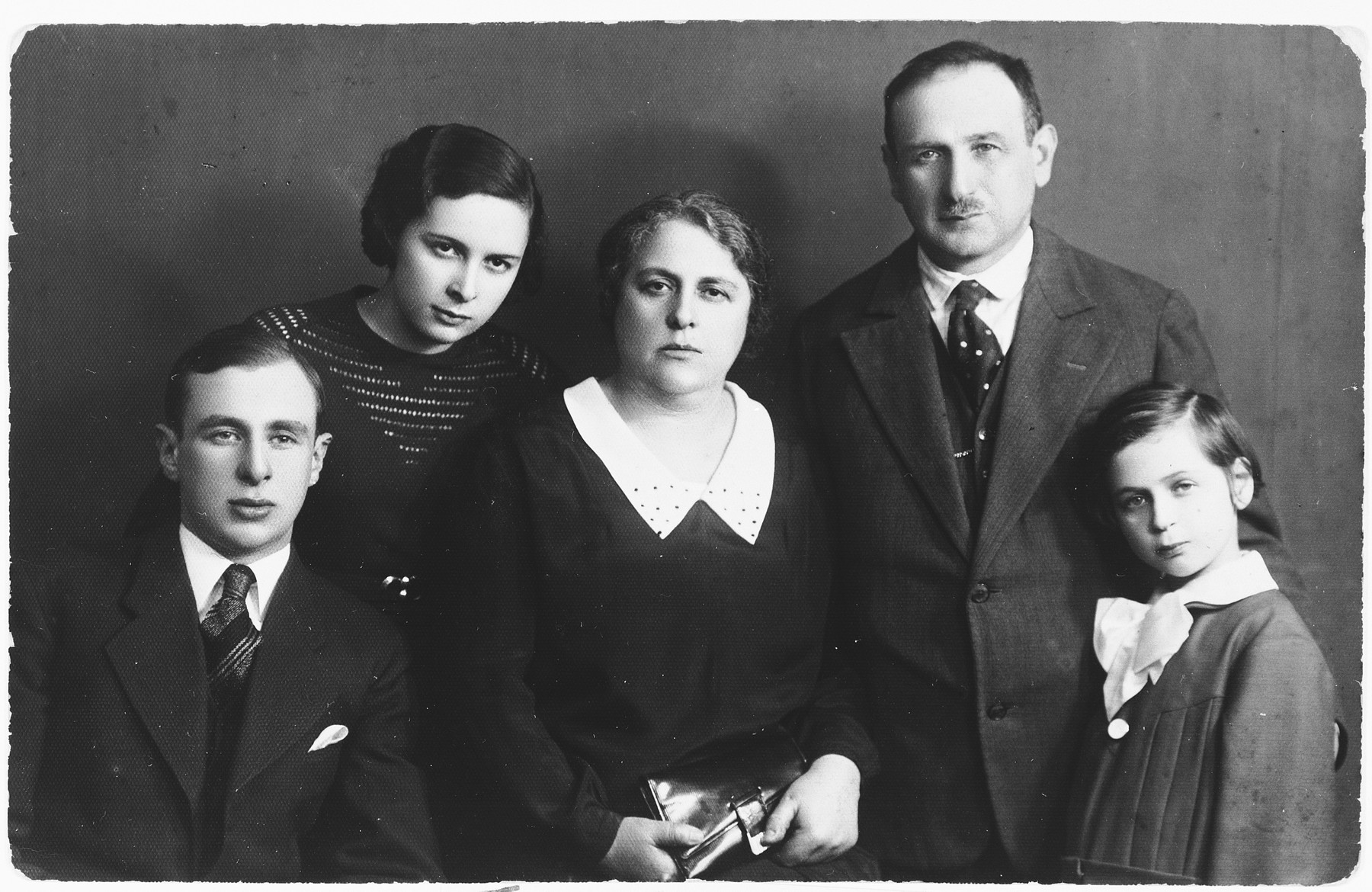 Studio portrait of the Puzerisky family in Vilna.  Pictured from left to right are: Morris, Emma, Riva, Meir and Gutta Puzerisky.
