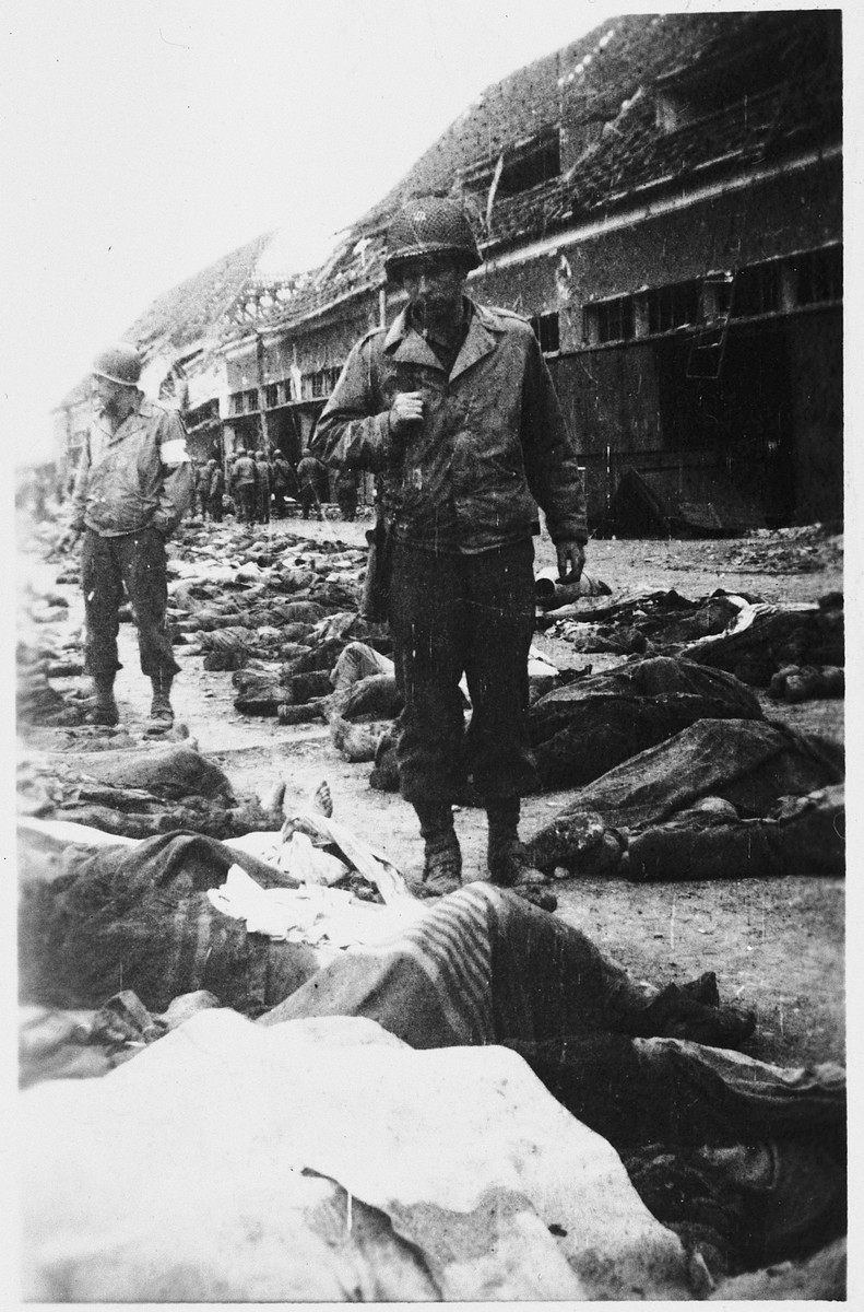 American soldiers walk past rows of dead bodies awaiting burial in the Nordhausen concentration camp.