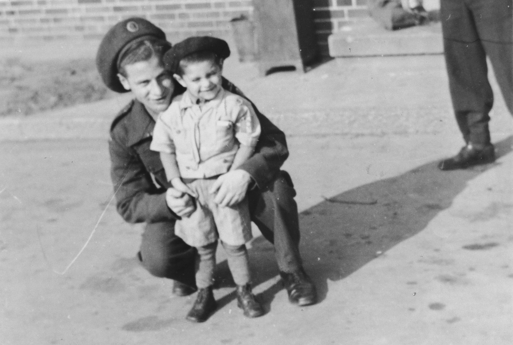 Jacob Zajac, a soldier in the Jewish Brigade, poses with a very young survivor in the Bergen-Belsen concentration camp.