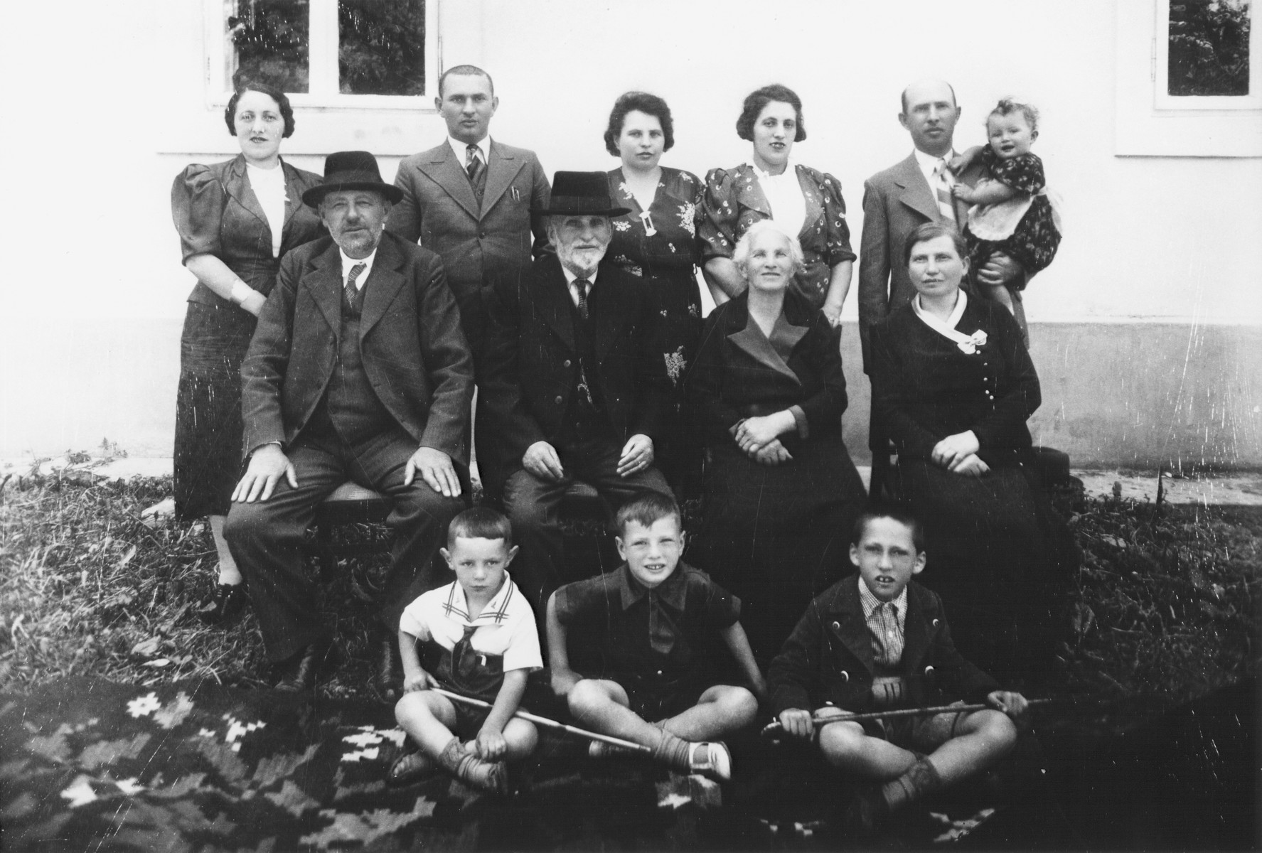 Portrait of a large family in Raduati, Romania taken on the occasion of visiting relatives from Canada.  From left to right.  Front row: Marice Kastner, Sidney Kastner, Osias (Osy) Kastner.  Middle row: David Schwamenthal, Srul Kastner, Malka Kastner and Sophie Kastner.  Back row: Edith Schwmenthal Kastner, Avrum Kastner, Rose (Koka) Kastner, Clara Schwamenthal Kastner, Yankel Kastner and Bella Kastner.  Avrum Kastner, Clara Kastner, Yankel Kastner, David Schwamenthal, and Srul and Malka Kastner all perished in Transnistria.  Sophie Kastner was shot and killed by the Iron Guard during the Radauti deportation in October 1941.  Rose and Sidney Kastner returned to Canada having been unsuccessful in persuading their families to join them.  Bella and Osias Kastner were brought up by their aunt Edith Kastner in Raduati following their liberation from Transnistria.