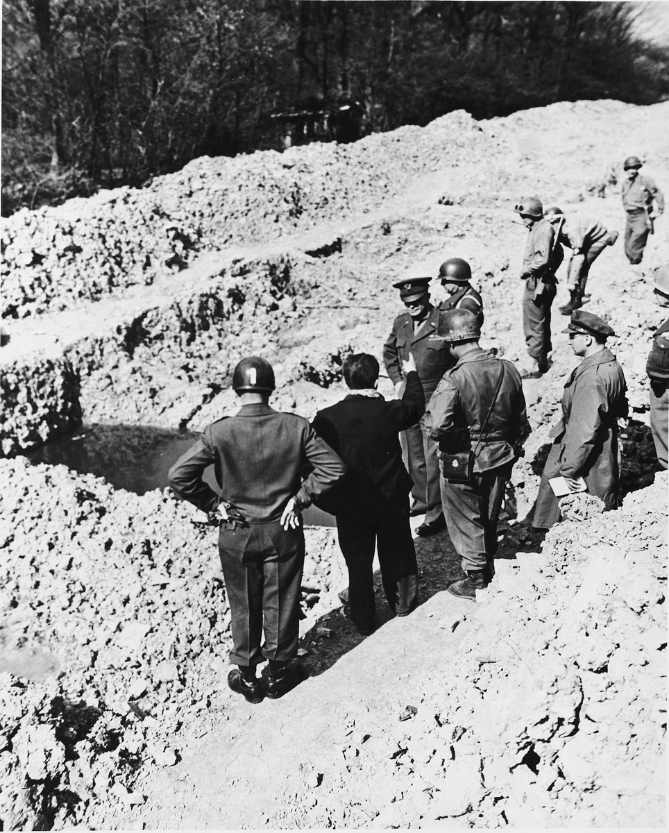 "An Austrian-Jewish survivor shows high-ranking U.S. Army officers a mass grave in the newly liberated Ohrdruf concentration camp.  Among those pictured are Generals Dwight D. Eisenhower, George Patton, Omar Bradley and Manton Eddy.  Also pictured is Jules Grad, correspondent for the U.S. Army newspaper, ""Stars and Stripes""."