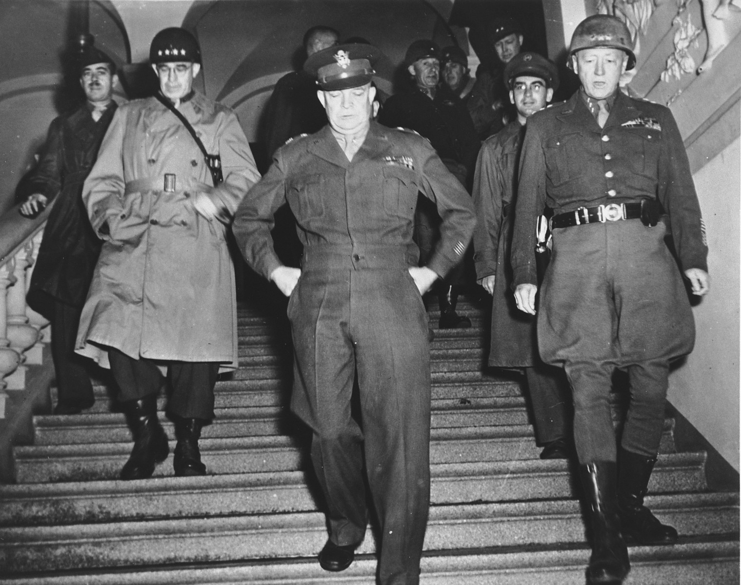 """High-ranking U.S. Army officers descend the stairs at an unidentified army headquarters in Europe.  Pictured from left to right are: Lt. Gen. Omar K. Bradley, Gen. Dwight D. Eisenhower, and Lt. Gen. George S. Patton.  Sgt. Jules Grad, correspondent for the newspaper, """"Stars and Stripes"""", walks behind Patton."""