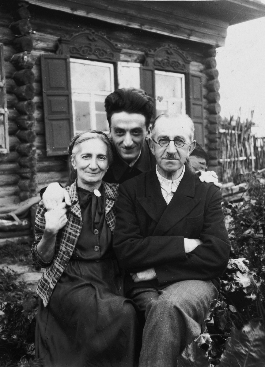 The Rafes family poses outside their home in the Ural Mountains where they were evacuated to during the war.  Pictured are Helena, Yulian and Itzhack Rafes.