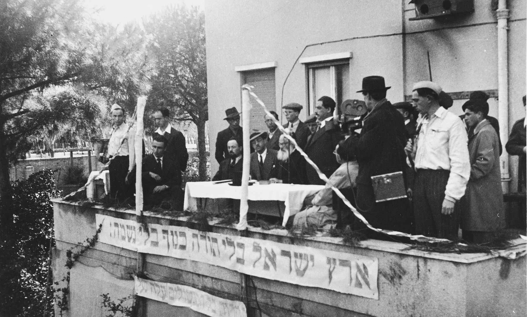 """DP religious leaders stand on the balcony of a building in Italy during a Zionist rally.  The banner reads, """"The Land of Israel without the Torah is like a body without a soul."""""""