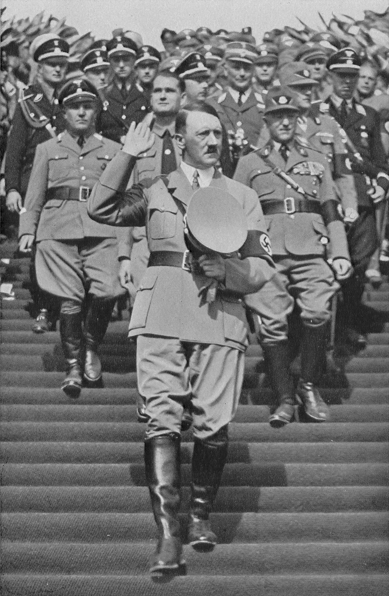 With his hand raised in a salute, Chancellor Adolf Hitler walks down the steps to the Zeppelinfeld during Reichsparteitag (Reich Party Day) ceremonies in Nuremberg.  Behind him stands Martin Bormann (left), Rudolf Hess (center), and Heinrich Himmler (behind Hess).