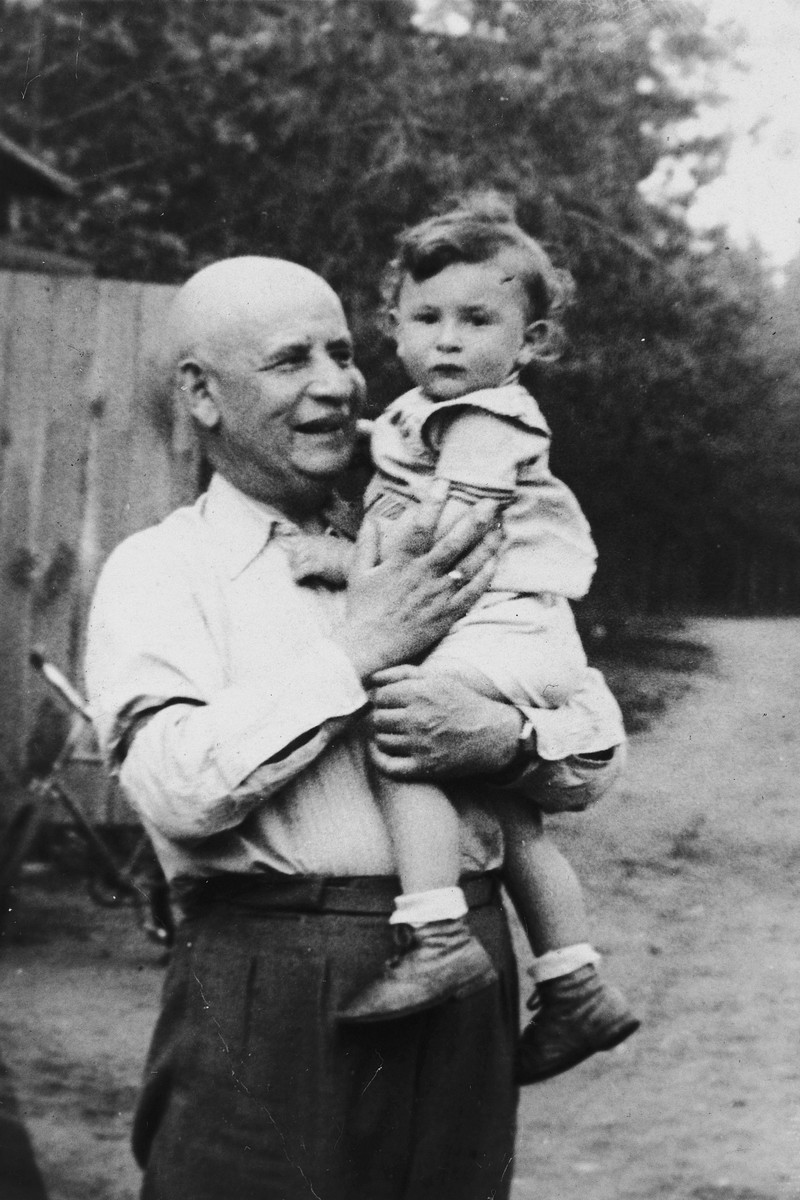A Jewish grandfather poses outside with his baby grandson.  Pictured is Cemach Telerant with his grandson Meir.