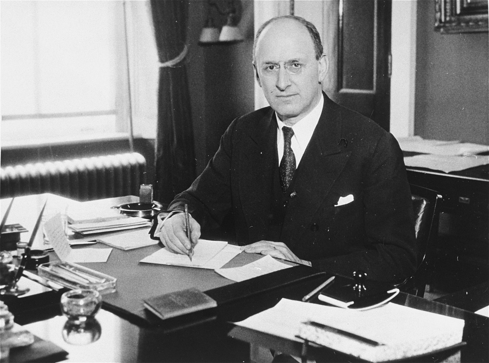 "Portrait of Henry Morgenthau Jr. at his desk in the U.S. Department of the Treasury.  Henry Morgenthau Jr. (1891-1967), served as Secretary of the Treasury under Franklin Roosevelt, and as such, was the highest ranking Jewish official in the administration.    In January 1944, after receiving a report prepared by his subordinates on ""the acquiescence of this government in the murder of the Jews,"" Morgenthau wrote a personal report to the President which led to the establishment of the War Refugee Board.   After the war he became Chairman of the United Jewish Appeal and served in that capacity until 1950."