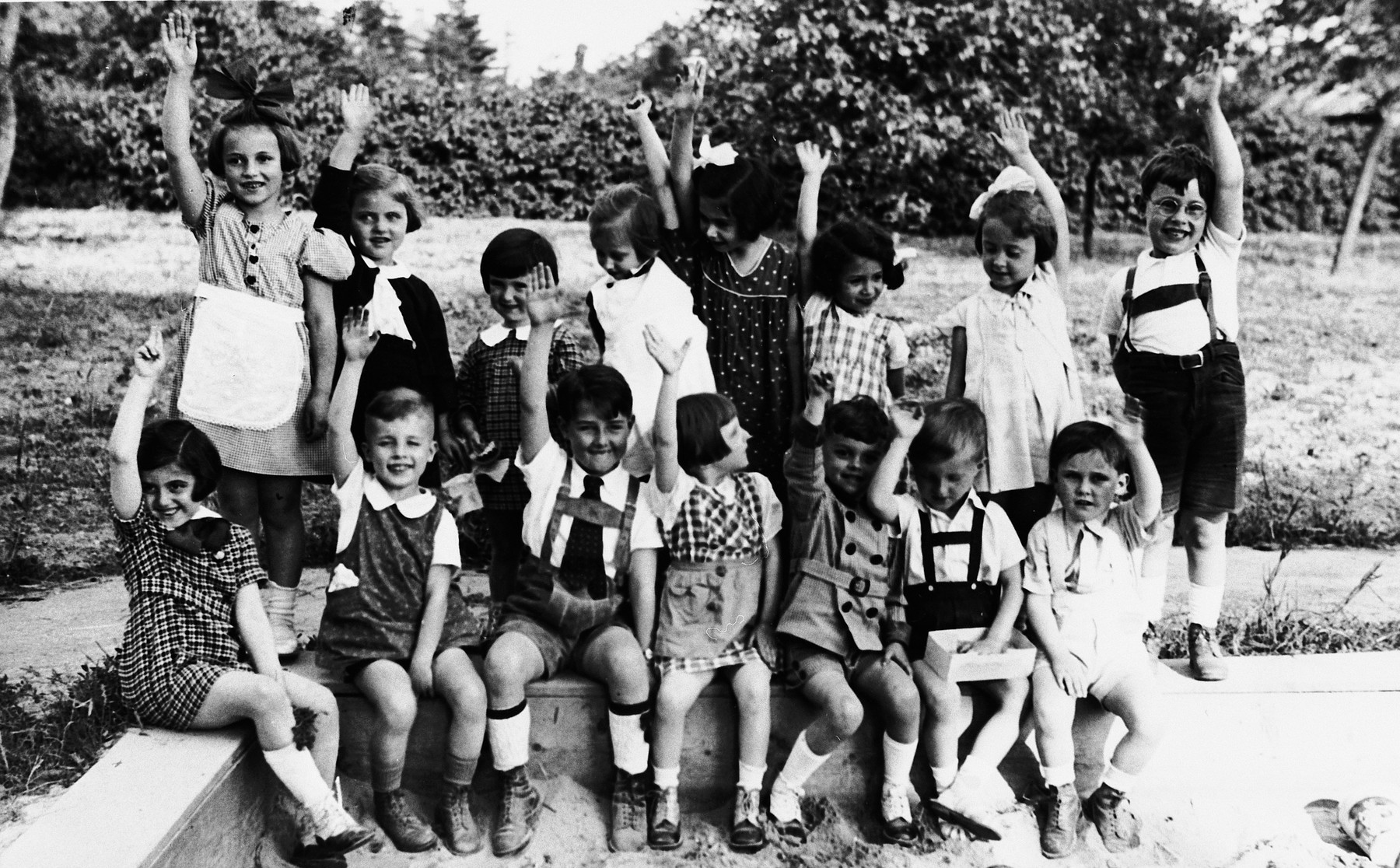 A group of elementary age children enthusiastically raise their arms while posing in a garden.  Kitty Weichherz is sitting in the first row on the far left.  This photo was taken from the diary of Kitty's life written by her father, Bela Weichherz.