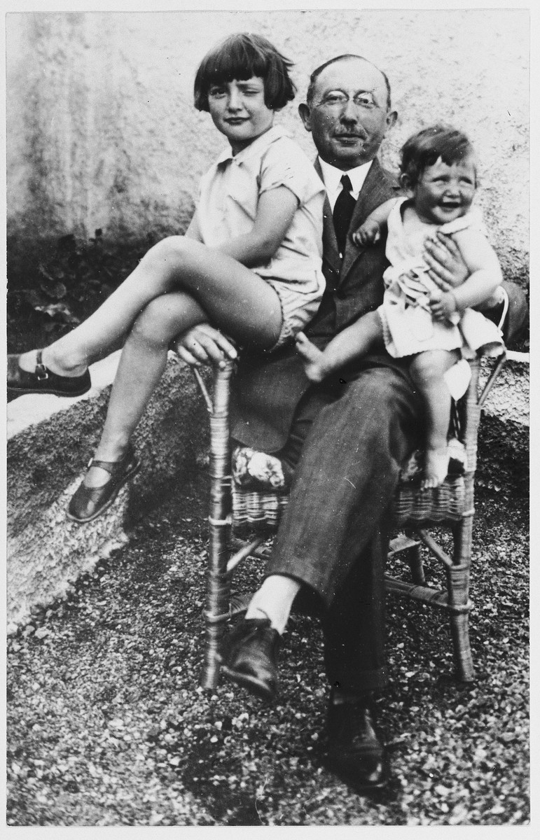 Doris and Eva Bermann sit on their grandfather's lap on a roof garden.