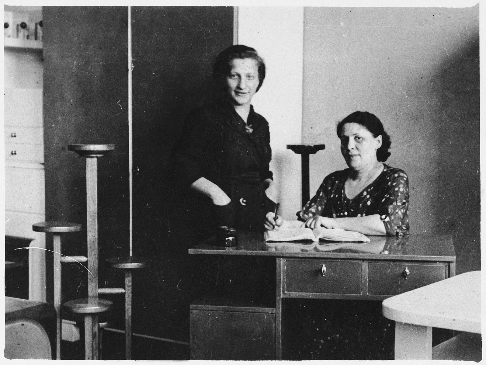 "Two Polish Jewish women pose in their furniture shop.  Among those pictured is Esther Federman.  The inscription on the back reads, ""Dear sister and brother-in-law.  This is my card with Esther, Ruchke's daughter.  She is with us and this is my factory.  Everlasting, Sheindel Krempel."""