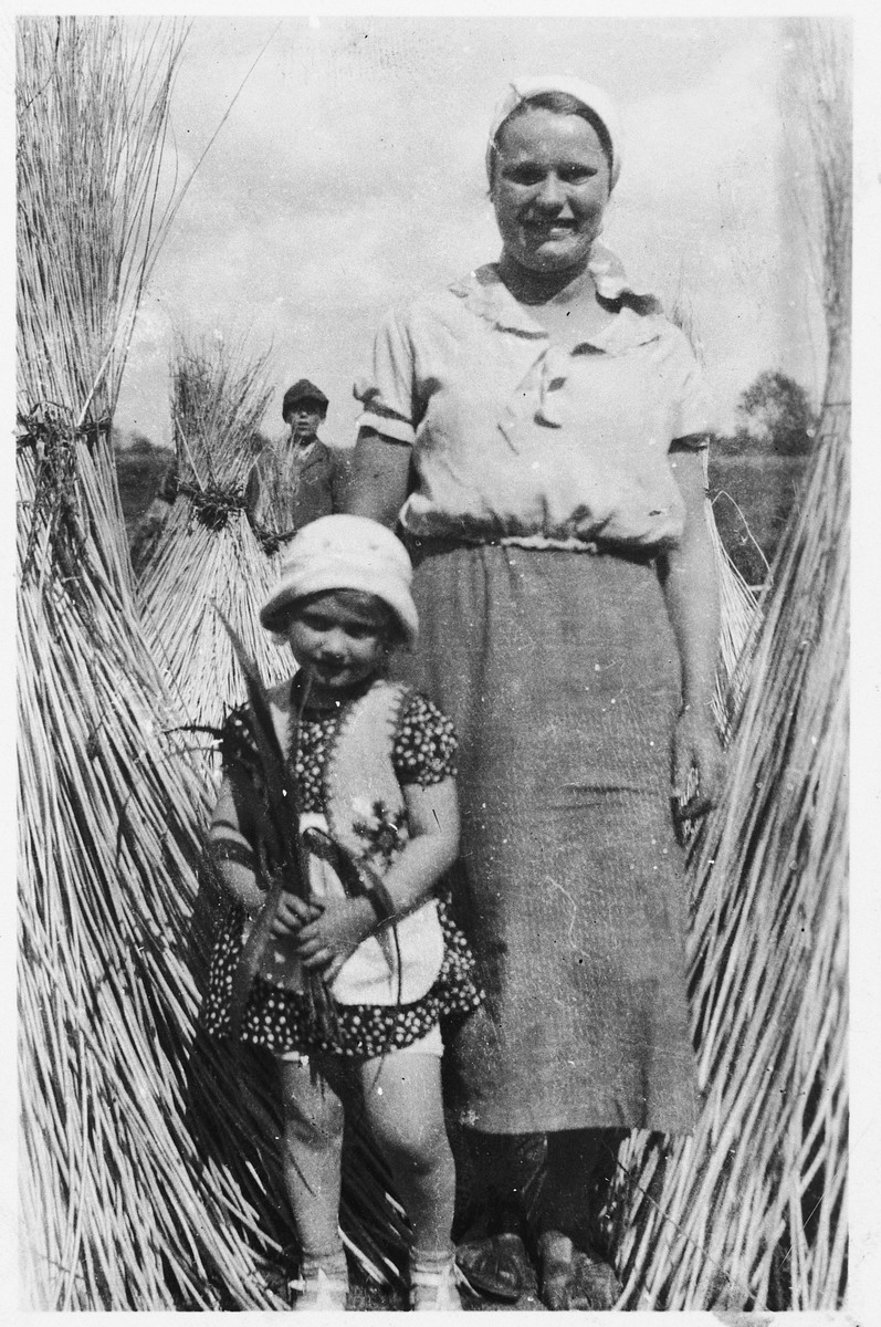 Yehudit Wagner and her Polish nurse stand among sheaves of wicker that will be used in her father's factory.