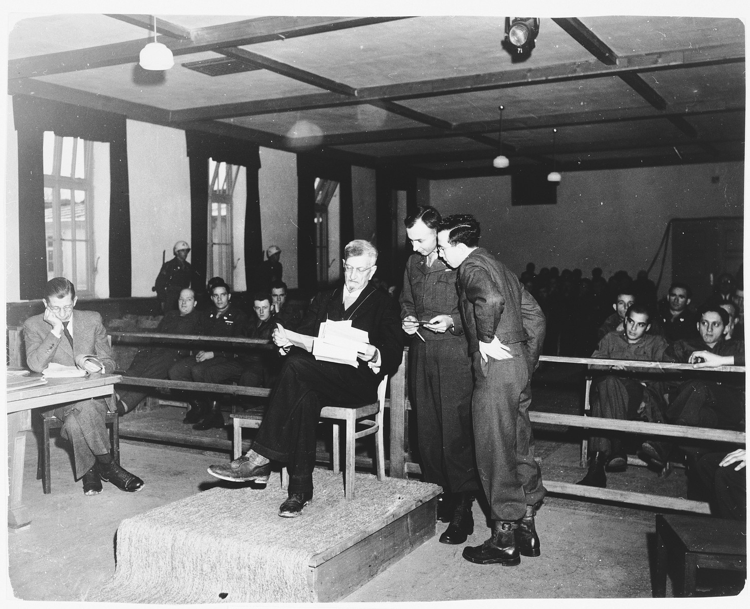 Defendant Dr. Klaus Schilling examines evidence on the stand in the Dachau trial.  He was responsible for performing malarial experiments on patients and was hanged in May 1946.