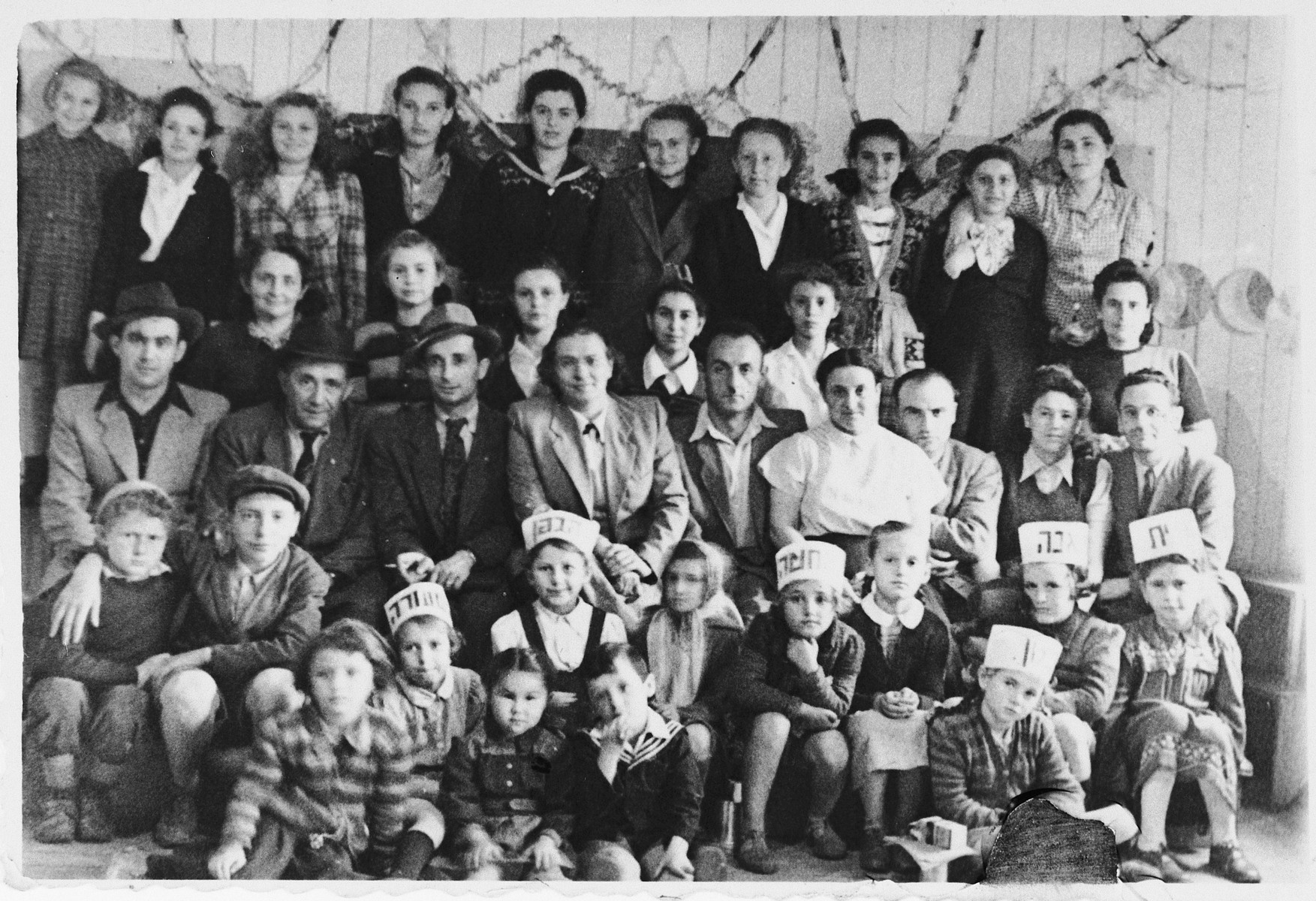 Students and teachers in the Tarbut school in Wels.  The youngest children are wearing crowns with Hebrew words written on them.