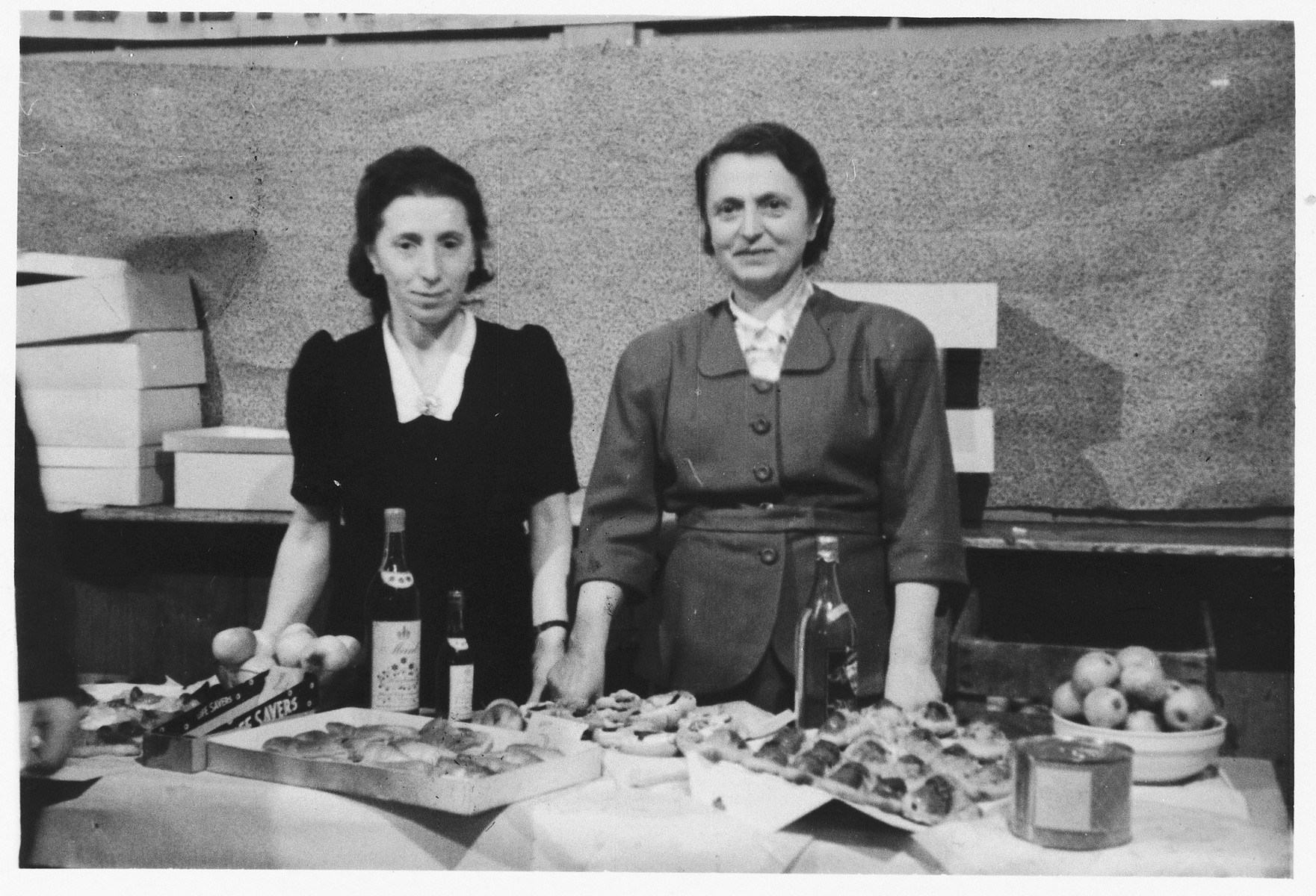 Two women stand behind a table laden with wine and delicacies in the Wels displaced persons' camp.  On the right is Chana Wagner, head of WIZO in Wels.