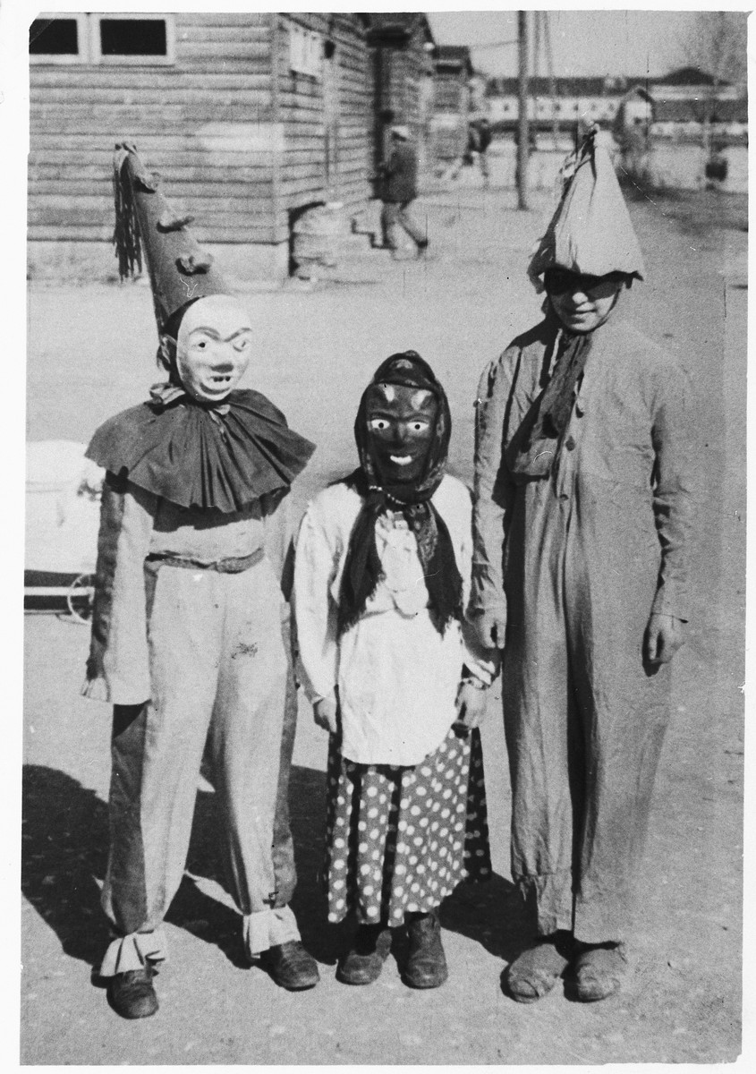 Three children in the Wels DP camp pose outside in their Purim costumes.