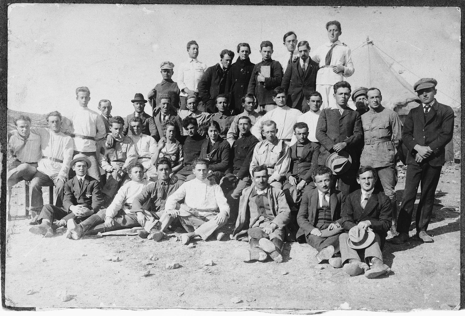 Pioneers in Palestine pose on a sandy plot where they hope to erect a new kibbutz.  Those pictured include Avraham Wagner.