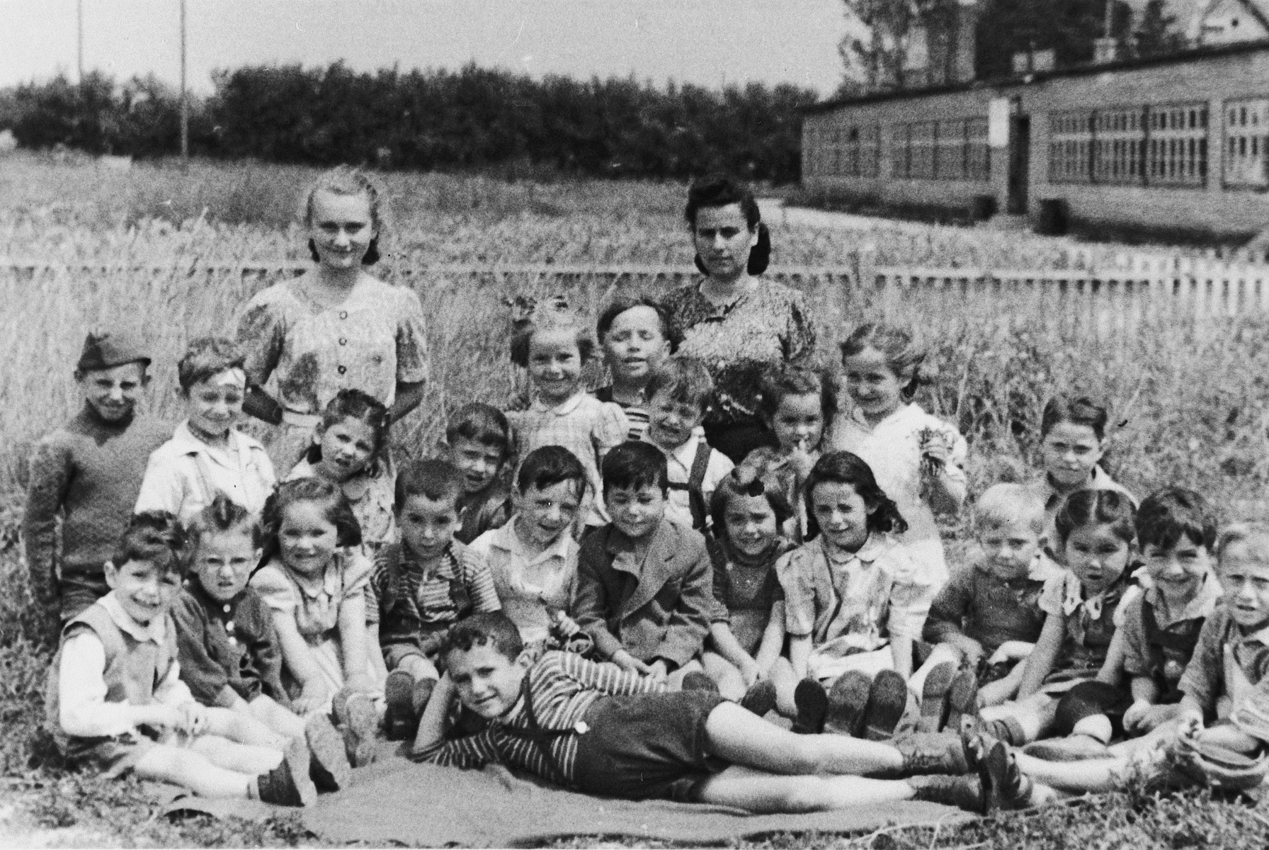 Kindergarteners in the Wels DP camp pose in an open field.  Yehudit Wagner who was working as a teacher's aide is in the back, left.